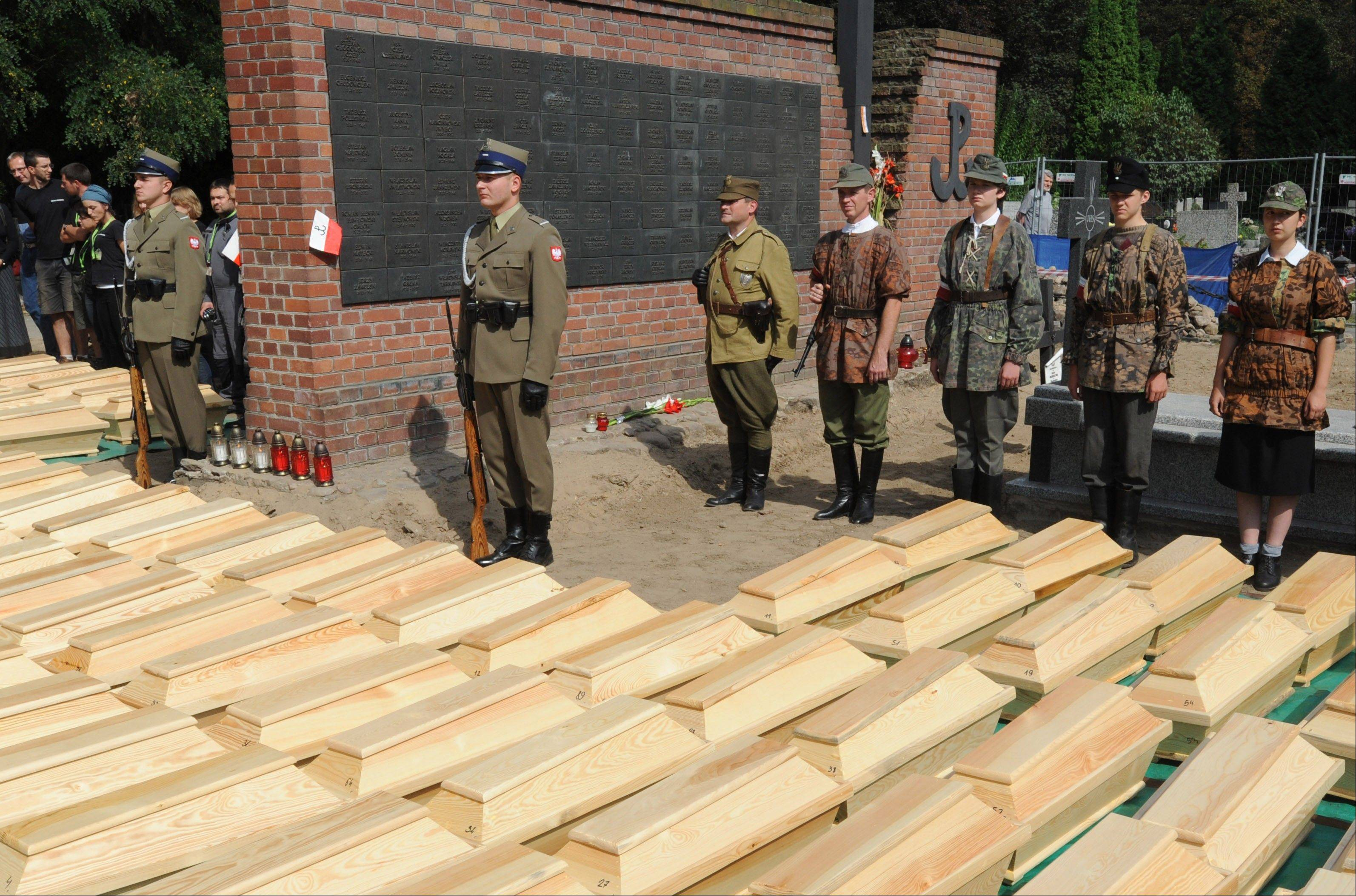 Soldiers and scouts stand in front of coffins containing remains of World War II heroes during a ceremony ending archeological works at the Powazki cemetery in Warsaw, Poland. More than a hundred skeletons of Poles murdered by the communist regime after World War II have been excavated from a secret mass grave on the edge of Warsaw's Powazki Military Cemetery during recent digging works. Historians hope to identify among them the remains of Witold Pilecki who volunteered to be an Auschwitz inmate to secretly gather evidence of atrocities there.
