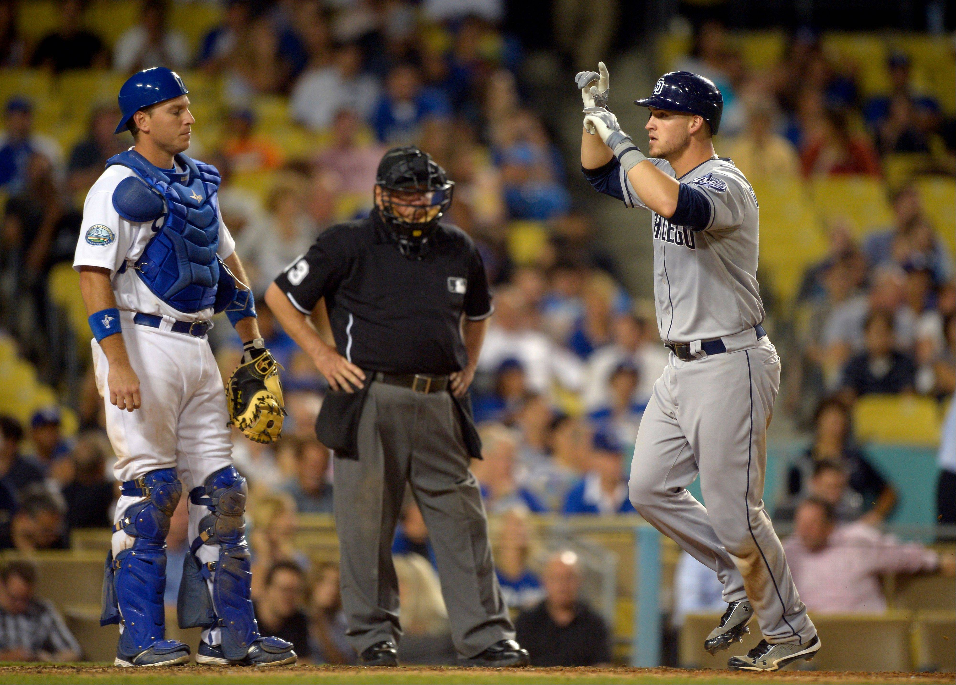 San Diego's Yasmani Grandal crosses the plate on his two-run home run as Dodgers catcher A.J. Ellis and home plate umpire Derryl Cousins watch during the eighth inning Tuesday in Los Angeles.