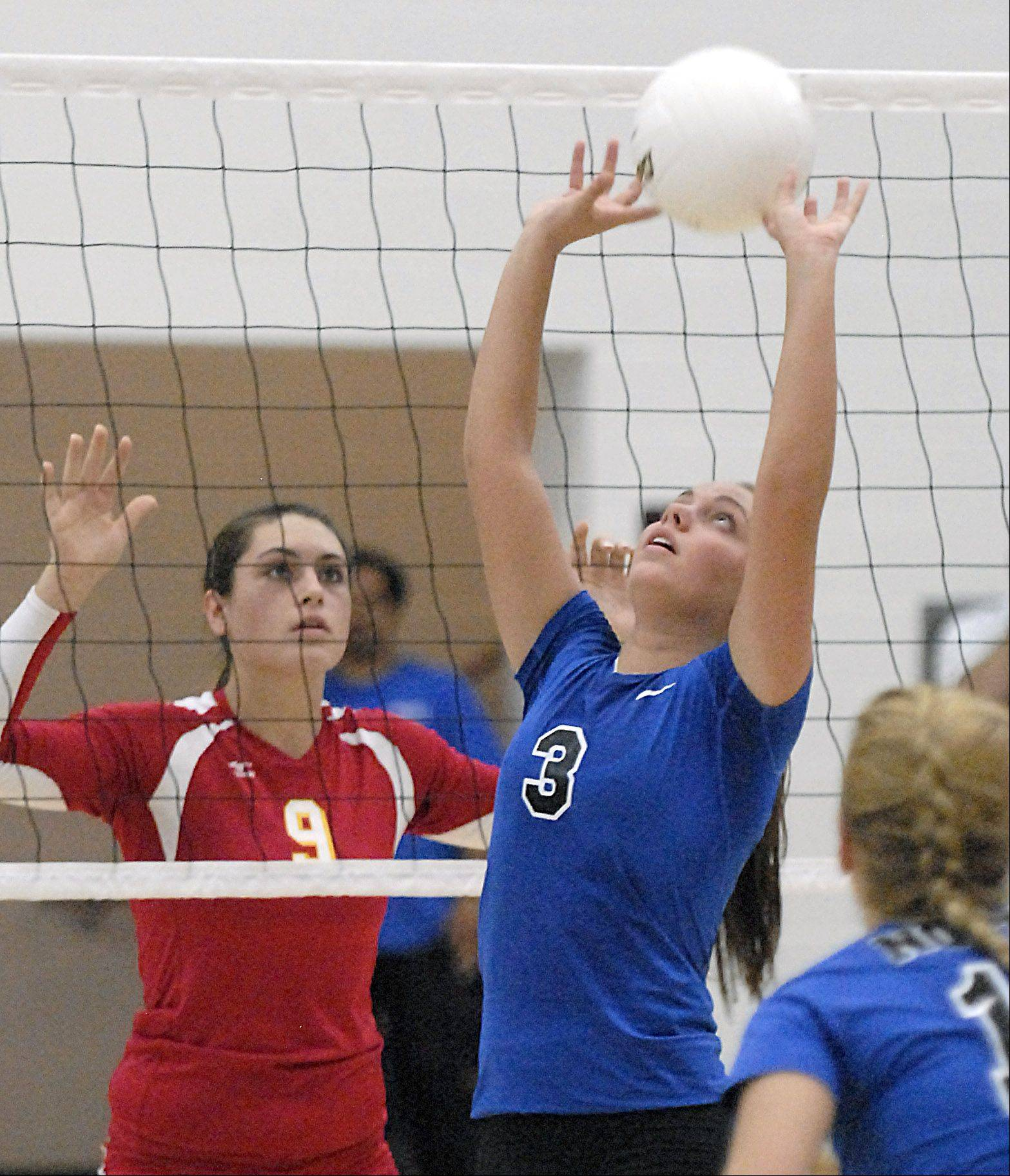 St. Charles North's Emily Belz sets up a spike as Batavia's Heather Meyer readies for it in game one on Tuesday, September 4.