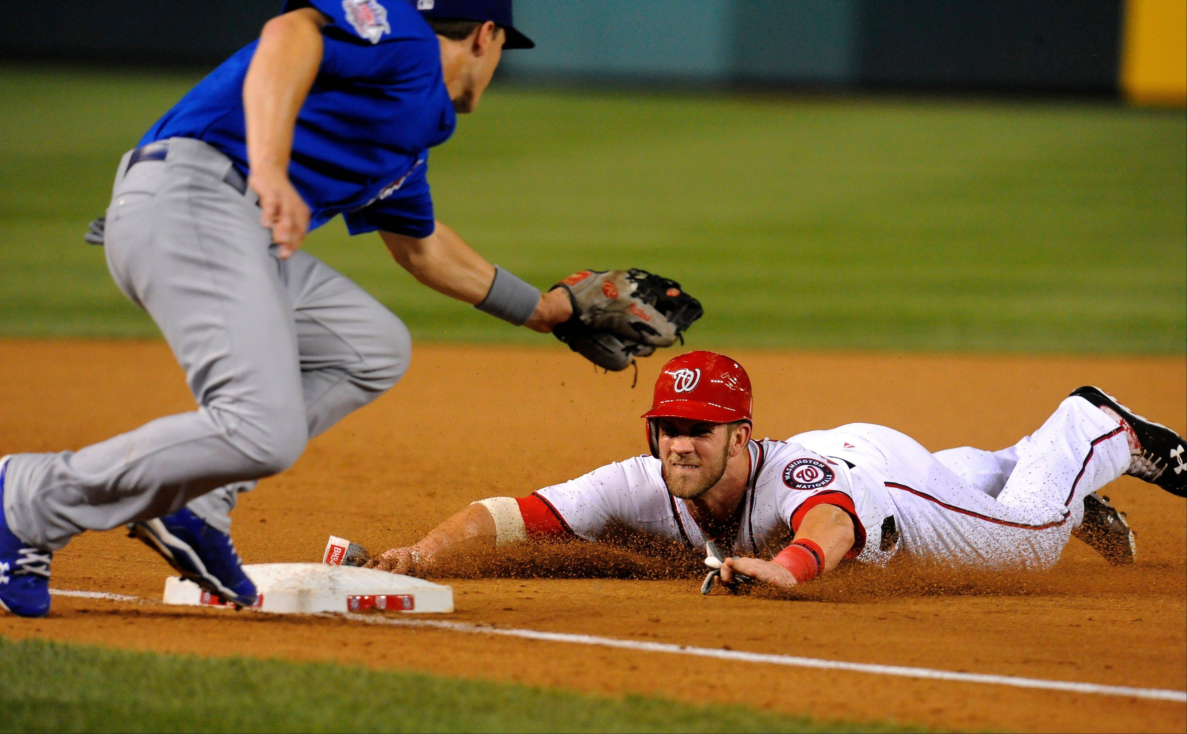 Washington Nationals outfielder Bryce Harper steals third base as the Cubs' Josh Vitters, left, applies a late tag during Tuesday's seventh inning.