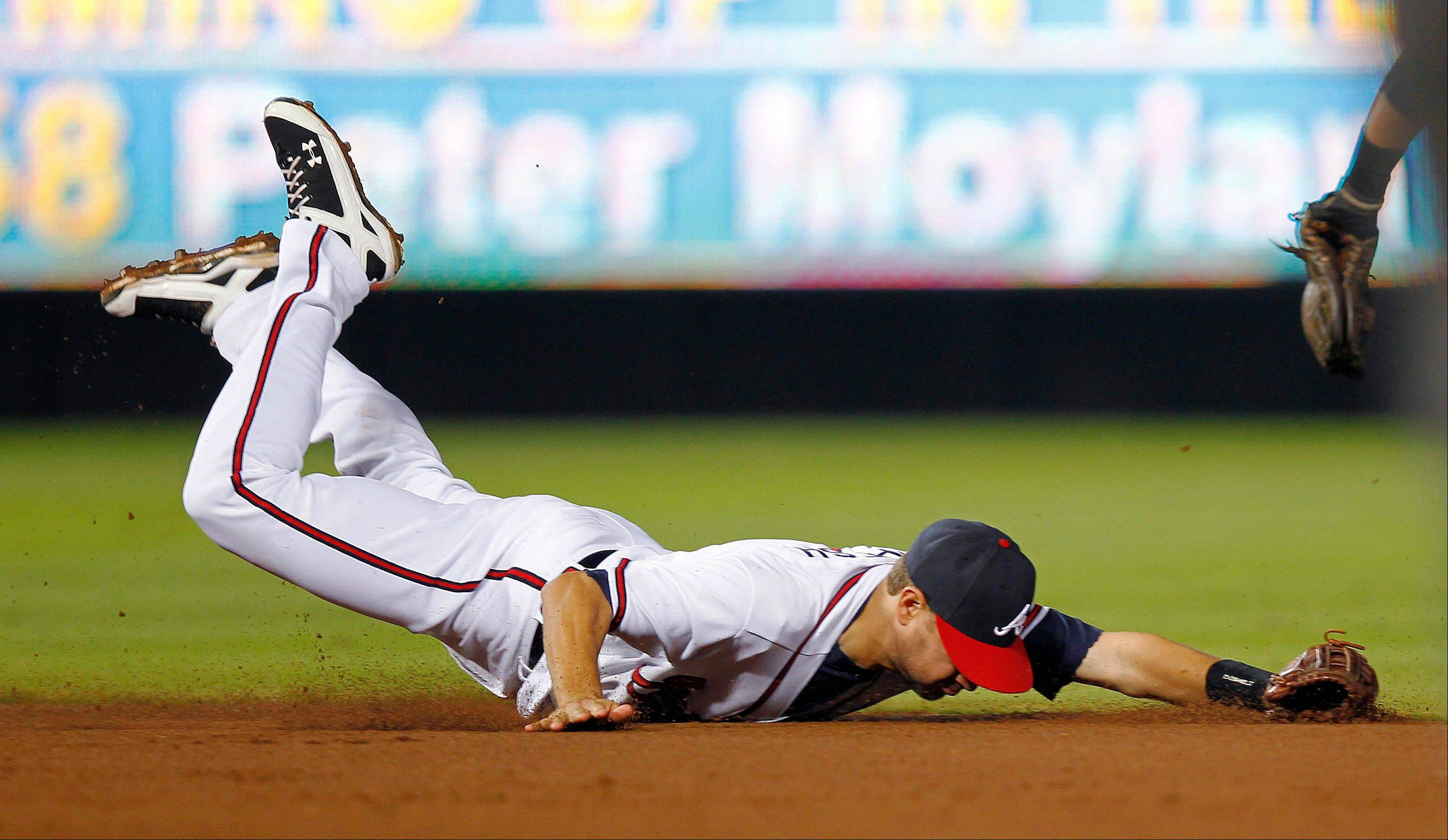 Braves shortstop Paul Janish can't reach a ball hit for a single by the Rockies' Wilin Rosario during the sixth inning Tuesday in Atlanta.