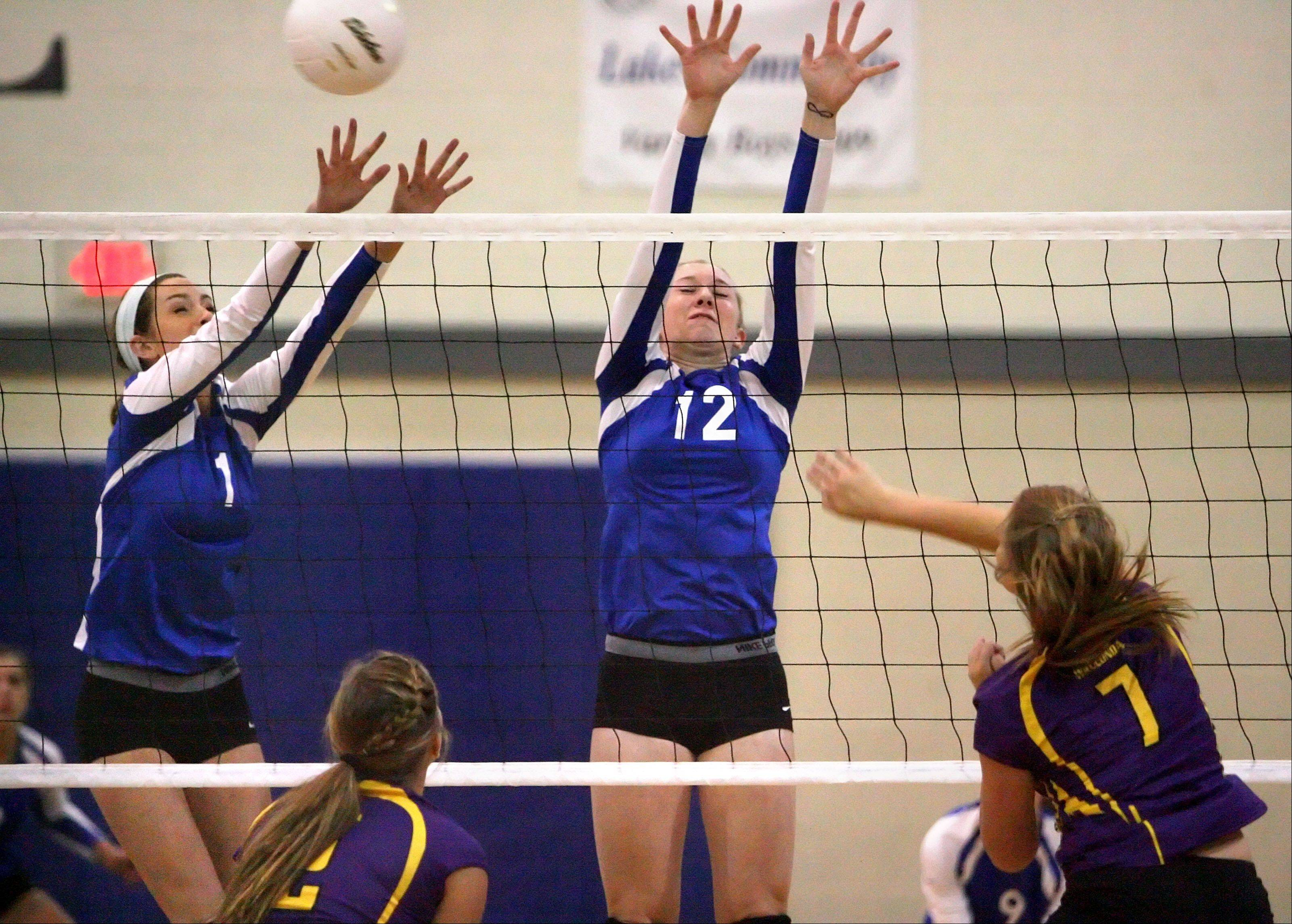 Wauconda's Lauren Soetaert, right, spikes one at Lakes' Haley Halberg, left, and Sarah Horner on Tuesday night at Lakes.