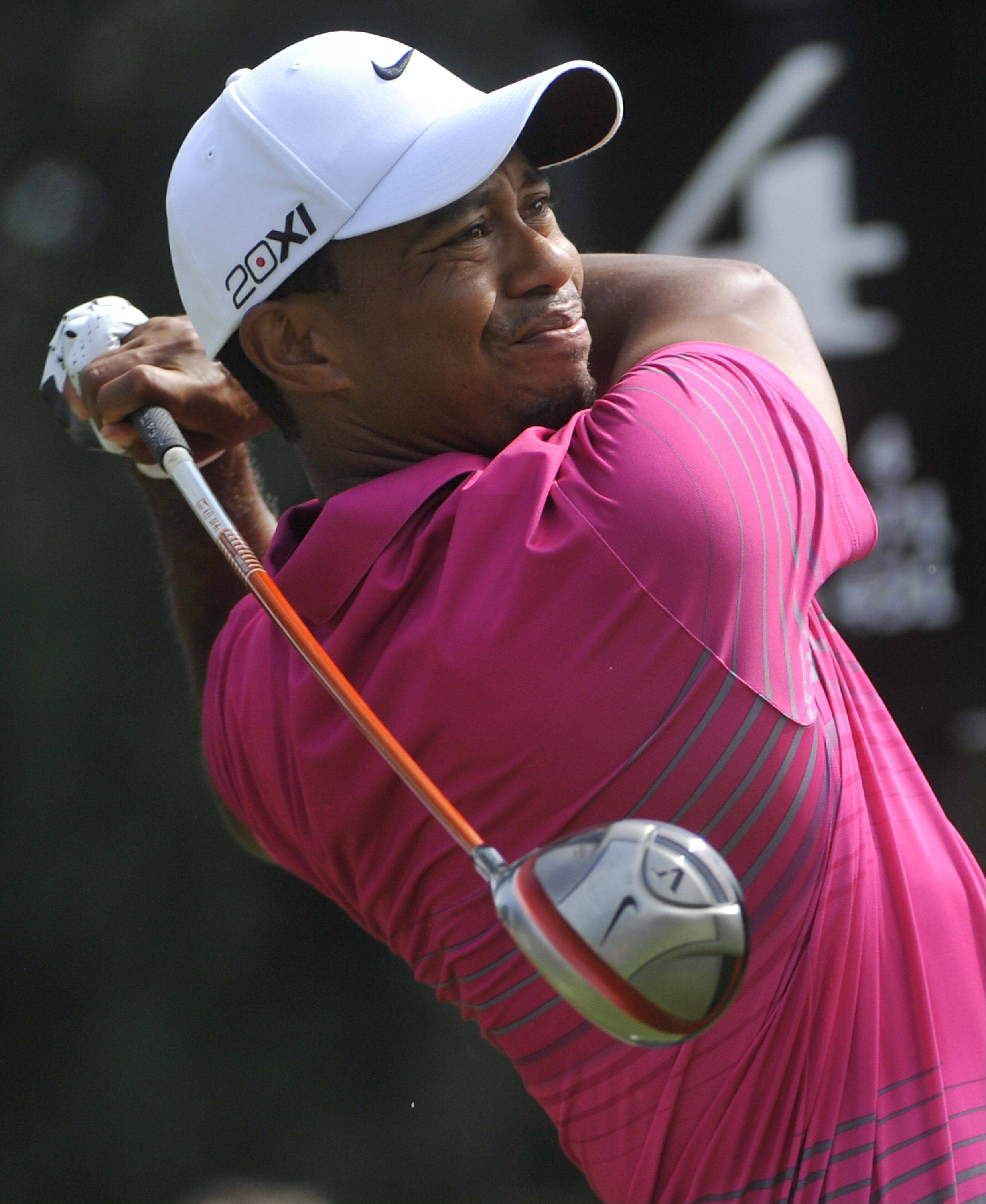 Tiger Woods hits his tee shot on the fourth hole, during the third round of the Bridgestone Invitational golf tournament, Saturday, Aug. 4, 2012, in Akron, Ohio.