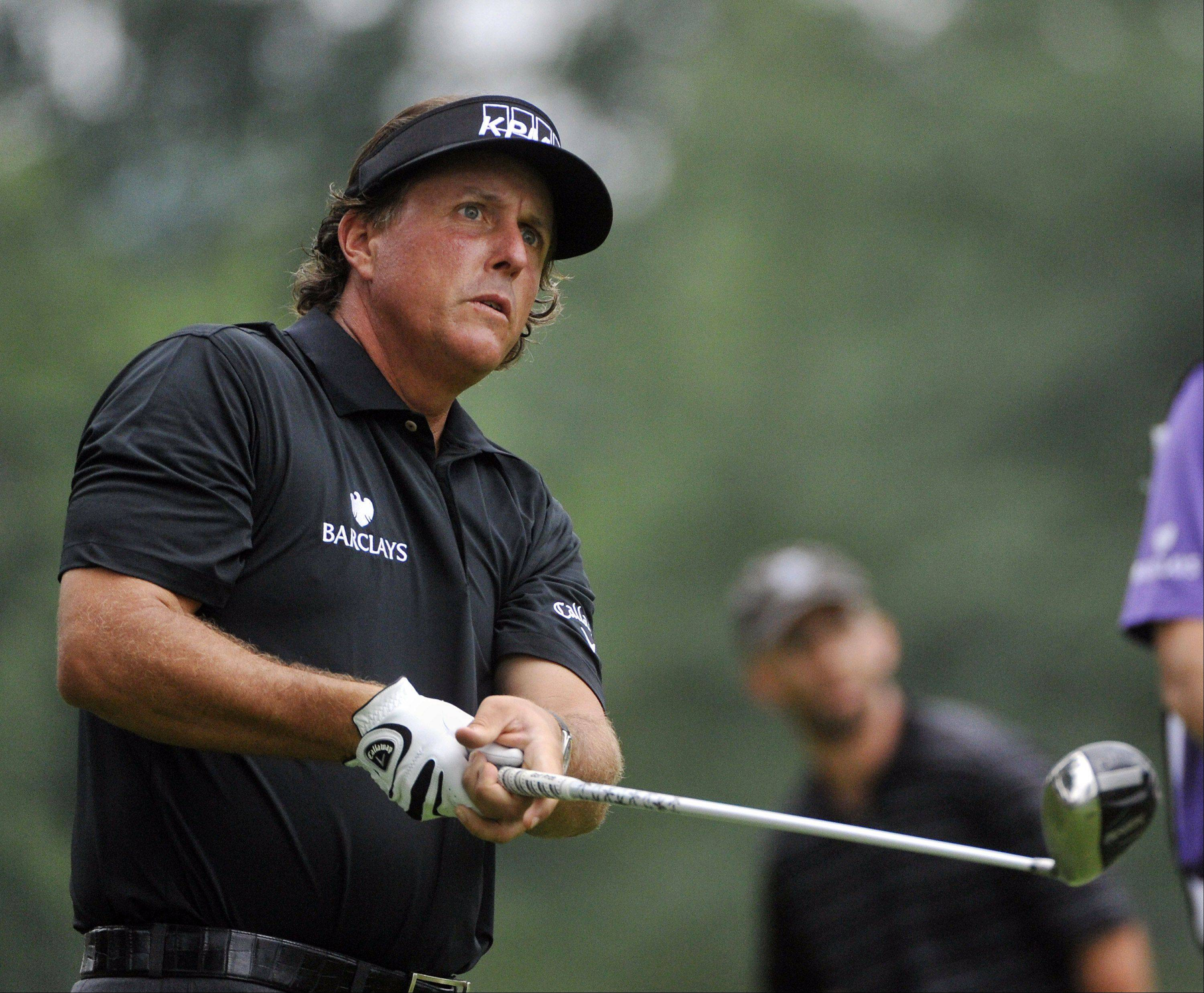 Phil Mickelson watches his tee shot on the 11th hole during the final round of the Bridgestone Invitational golf tournament at Firestone Country Club in Akron, Ohio, Sunday, Aug. 5, 2012.