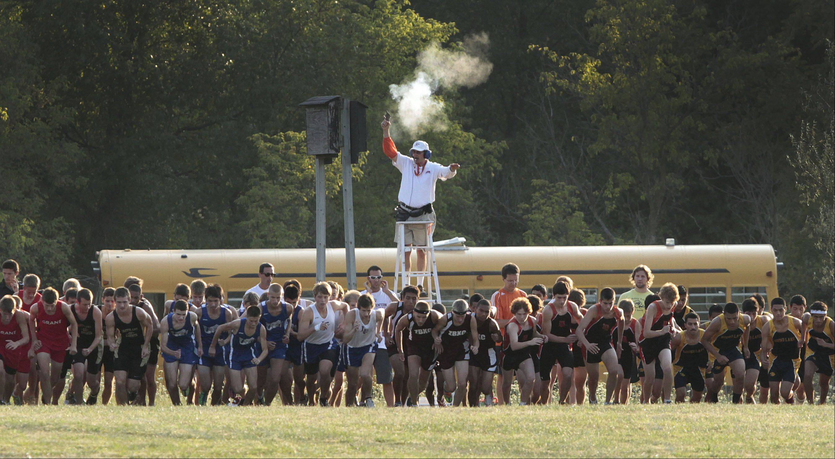The starter signals the start of the Lake County boys cross country meet Wednesday at Lakewood Forest preserve near Wauconda.