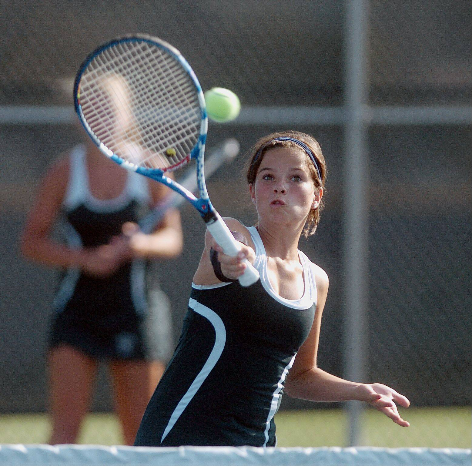 Glenbard West's Ali Bush returns the ball during her doubles match against Naperville North Thursday.