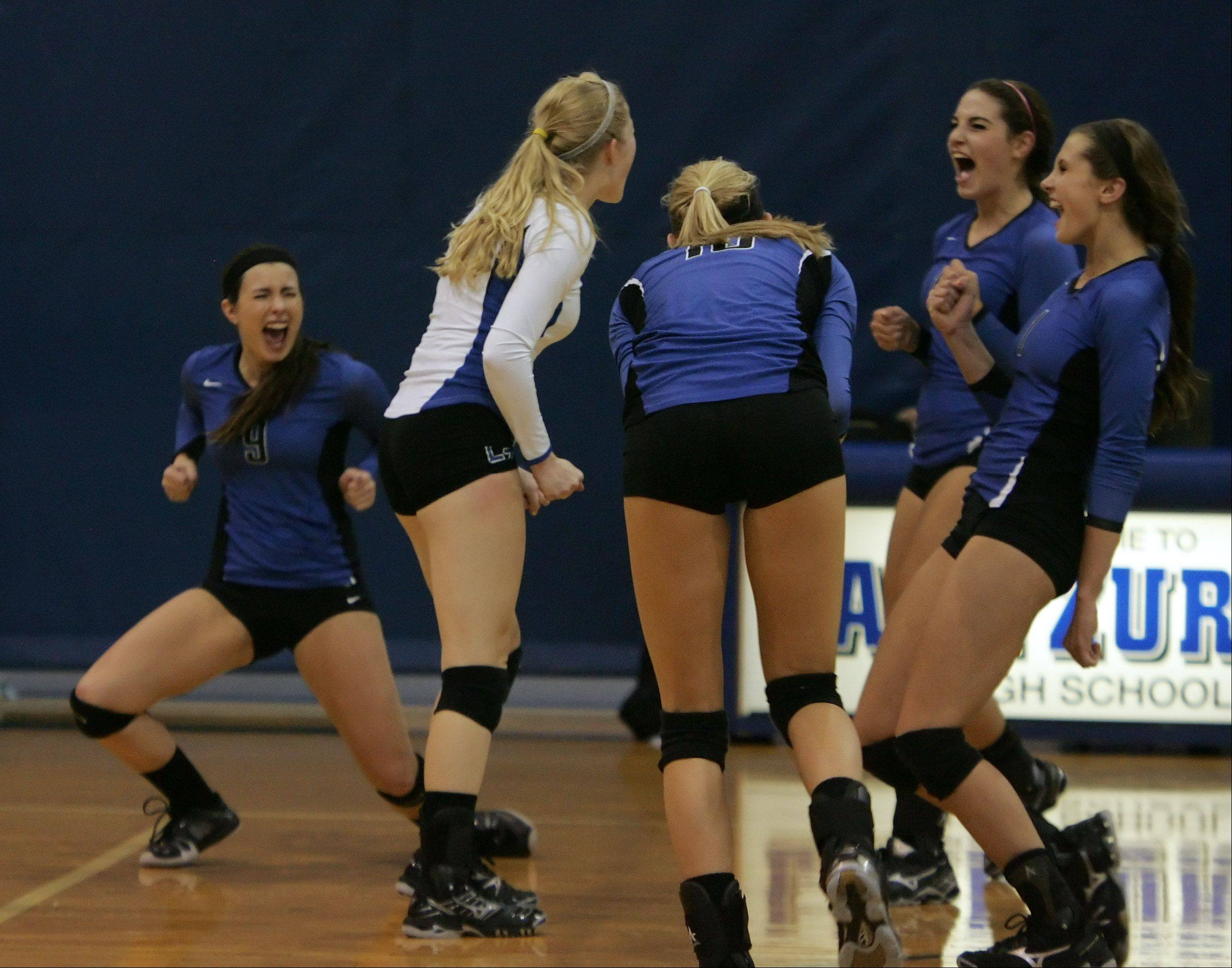 Lake Zurich players celebrate their first-game win against Prairie Ridge Tuesday.
