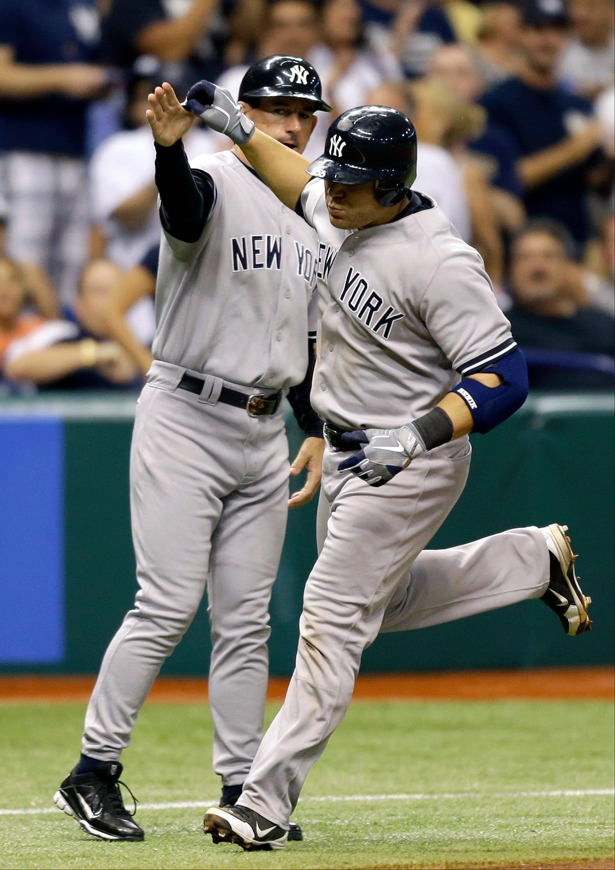 The Yankees� Russell Martin, right, high-fives third base coach Rob Thomson after hitting a sixth-inning home run off Tampa Bay Rays starting pitcher Matt Moore on Wednesday in St. Petersburg, Fla.