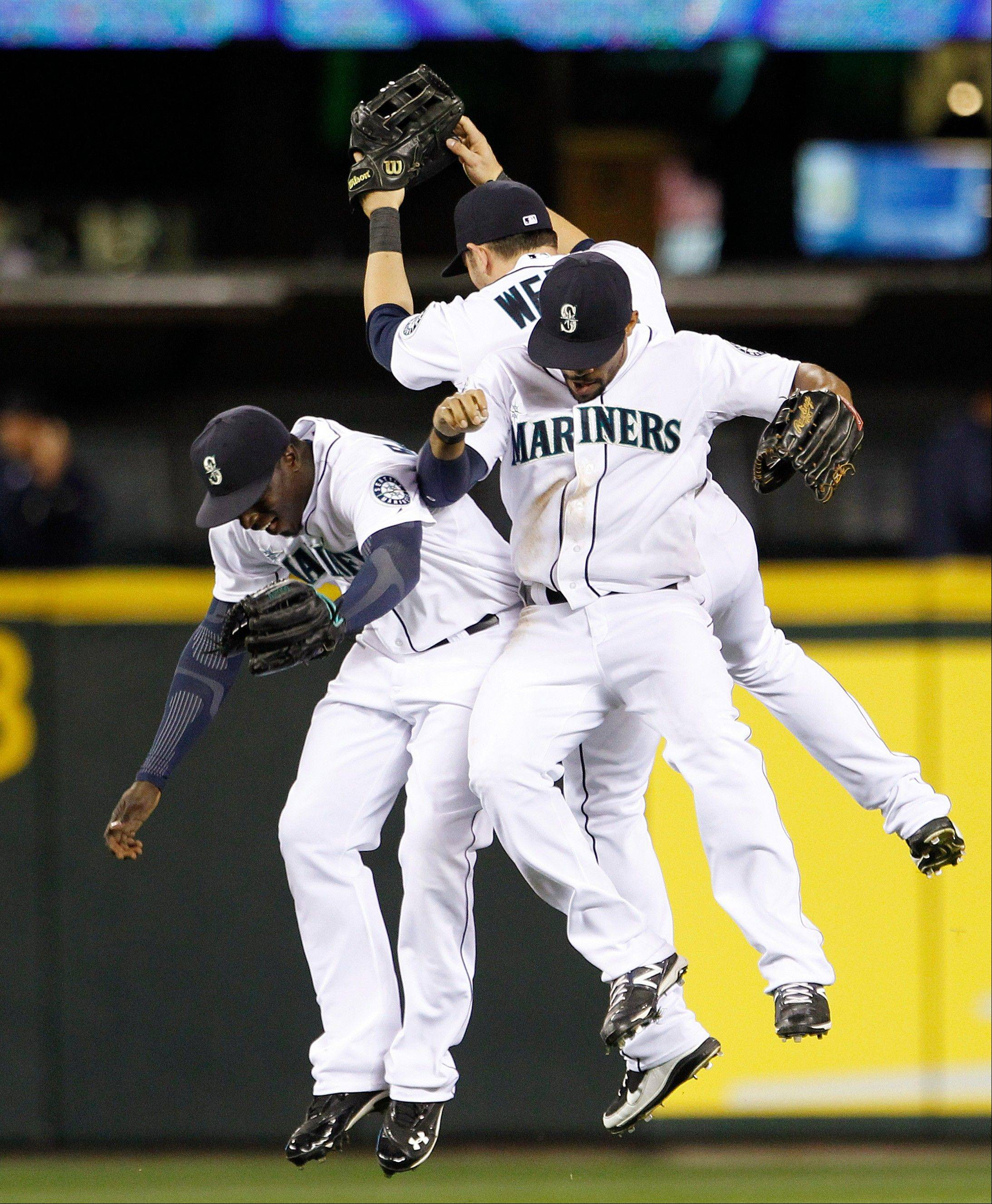 Seattle Mariners outfielders Trayvon Robinson, left, Casper Wells and Eric Thames celebrate after the team beat the Boston Red Sox on Wednesday at home.