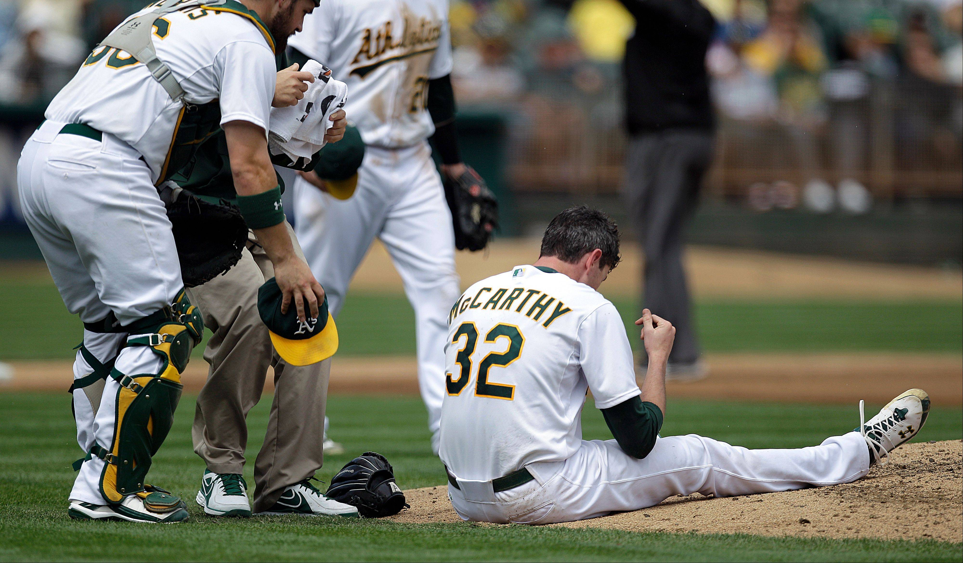 Oakland Athletics catcher Derek Norris, left, comes to the aid of pitcher Brandon McCarthy (32) who was hit in the head by a ball hit by Los Angeles Angels� Erick Aybar in the fourth inning of a baseball game on Wednesday in Oakland, Calif. McCarthy left the game after the incident.