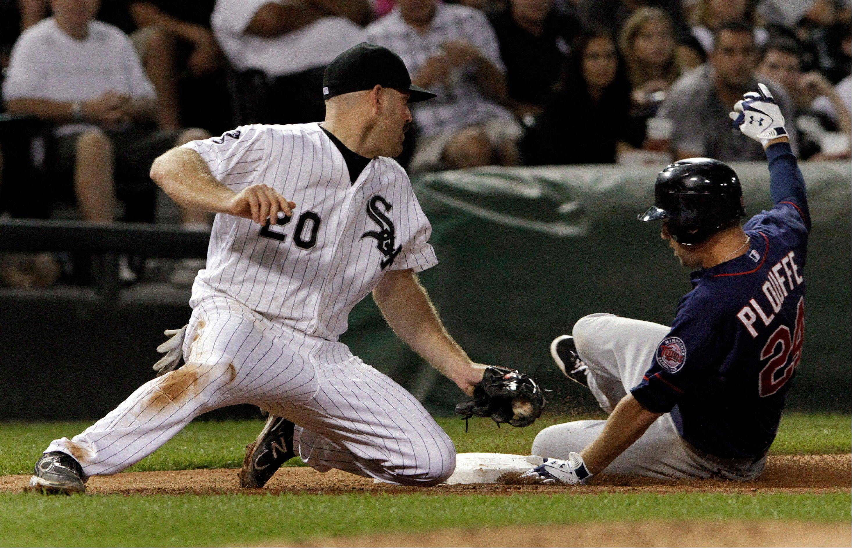 Minnesota Twins� Trevor Plouffe gets under the tag of White Sox third baseman Kevin Youkilis with an RBI triple during Tuesday�s fifth inning.