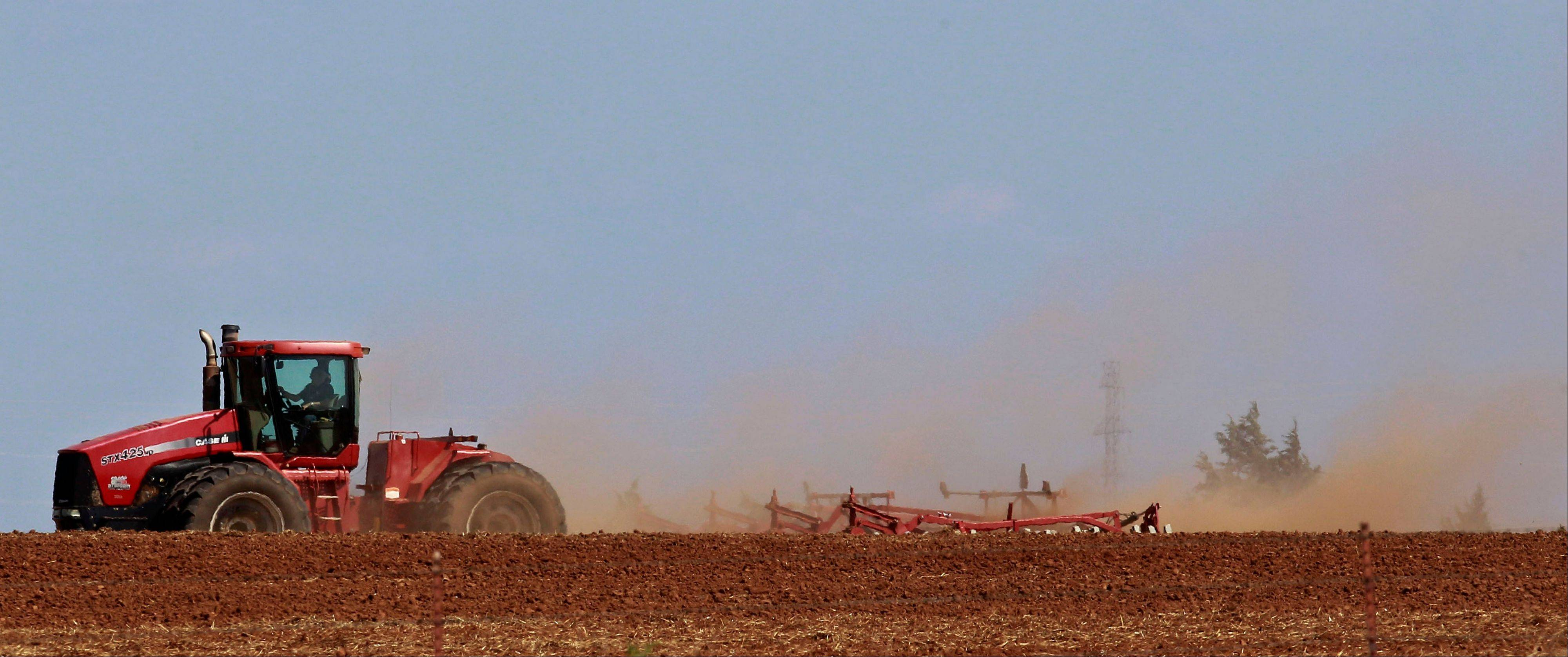 Dust swirls behind his tractor as a farmer works his dry field near Edmond, Okla., Thursday, Aug. 30, 2012. Exceptional drought conditions have eased slightly in parts of Oklahoma, though most of the state remains in extreme drought.