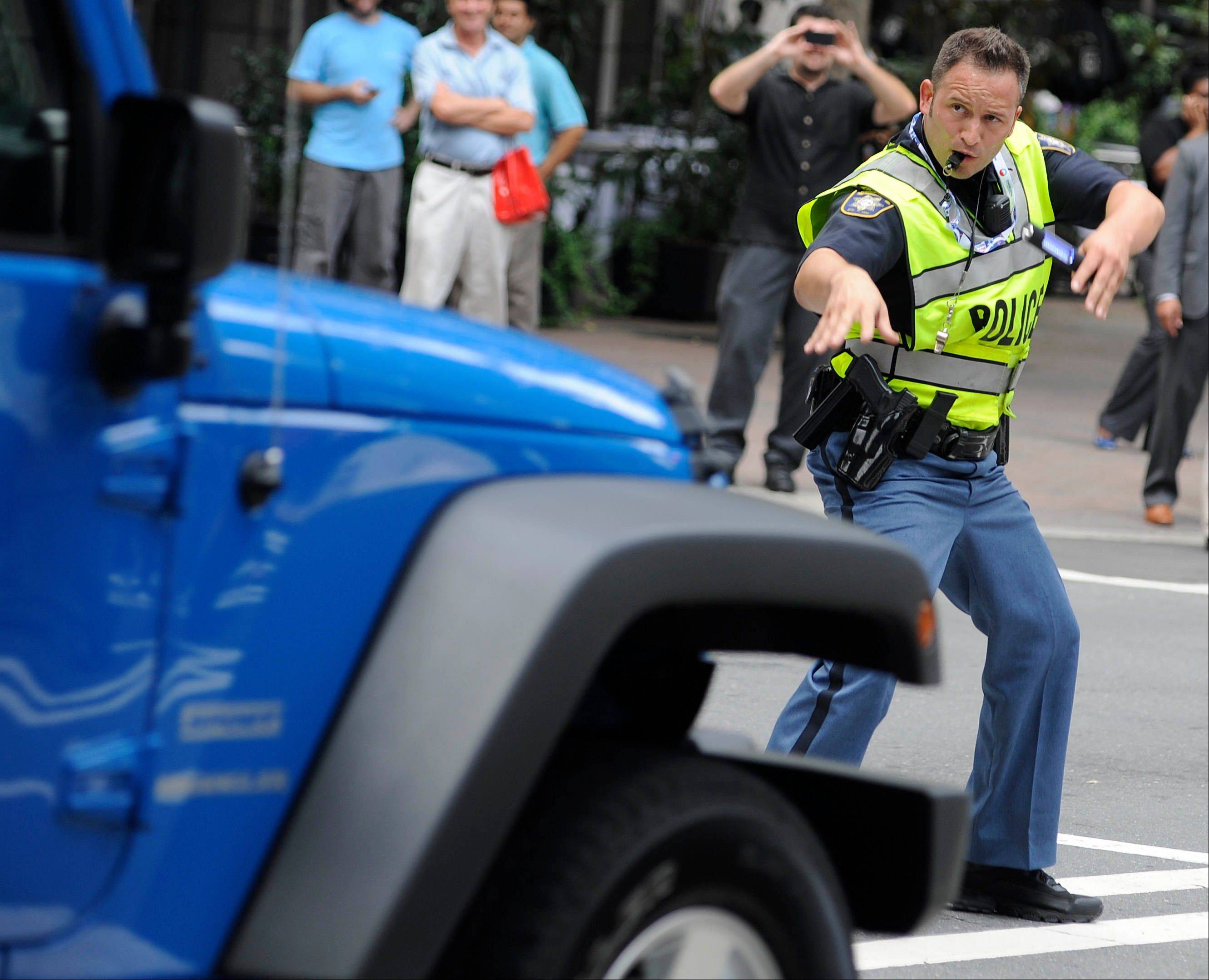 Clayton County (Ga.) Sheriff's Deputy John Strutko dances as he directs traffic Wednesday, Sept. 5, 2012, in Charlotte, N.C., during the second day of the Democratic National Convention.