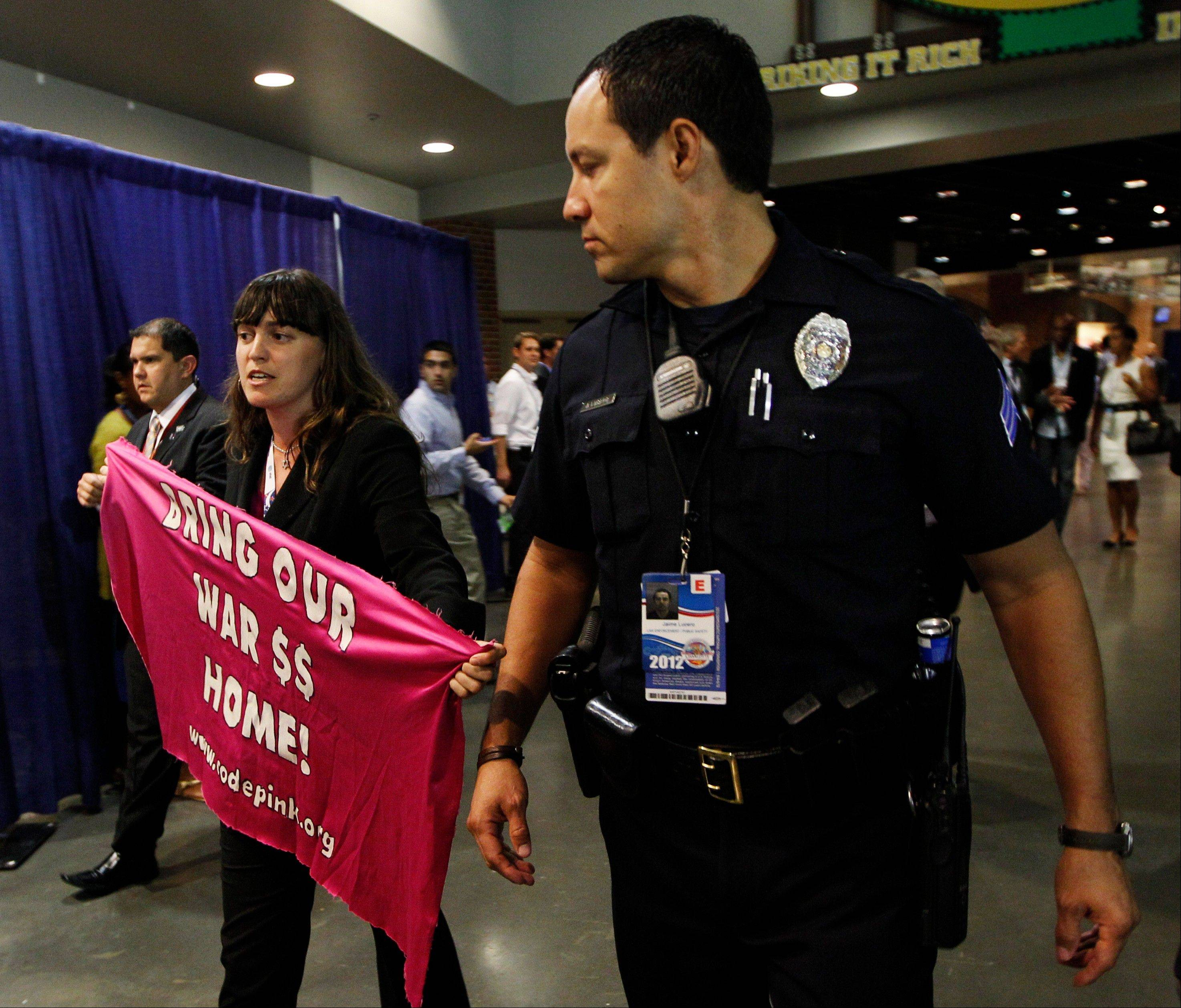 A protester is escorted out of the Timer Warner Arena by a police officer during the Democratic National Convention in Charlotte, N.C., on Wednesday, Sept. 5, 2012.