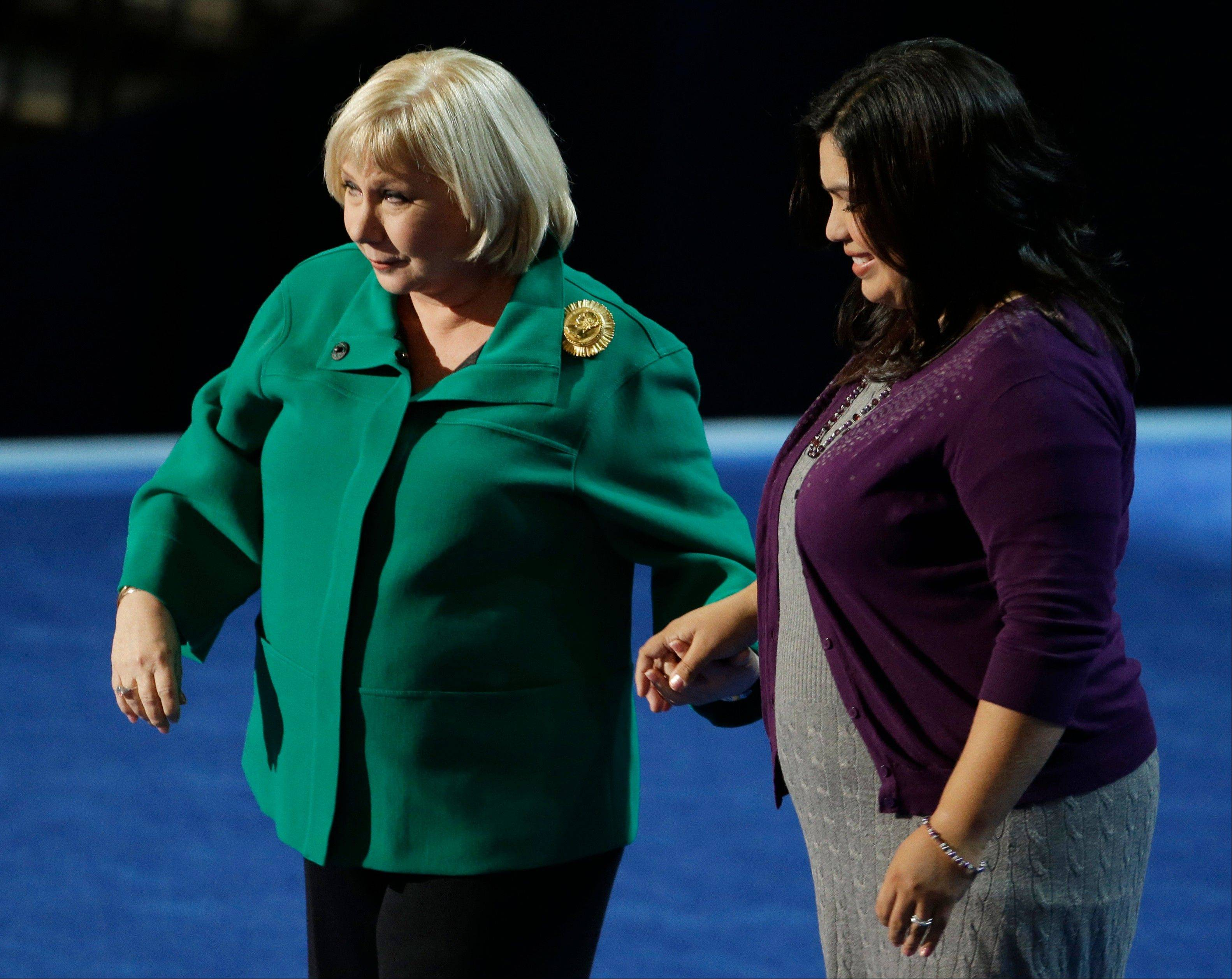 Journalist and talk show host Cristina Saralegui, left, hold hands with DREAM Act activist Benita Veliz at the Democratic National Convention in Charlotte, N.C., on Wednesday, Sept. 5, 2012.