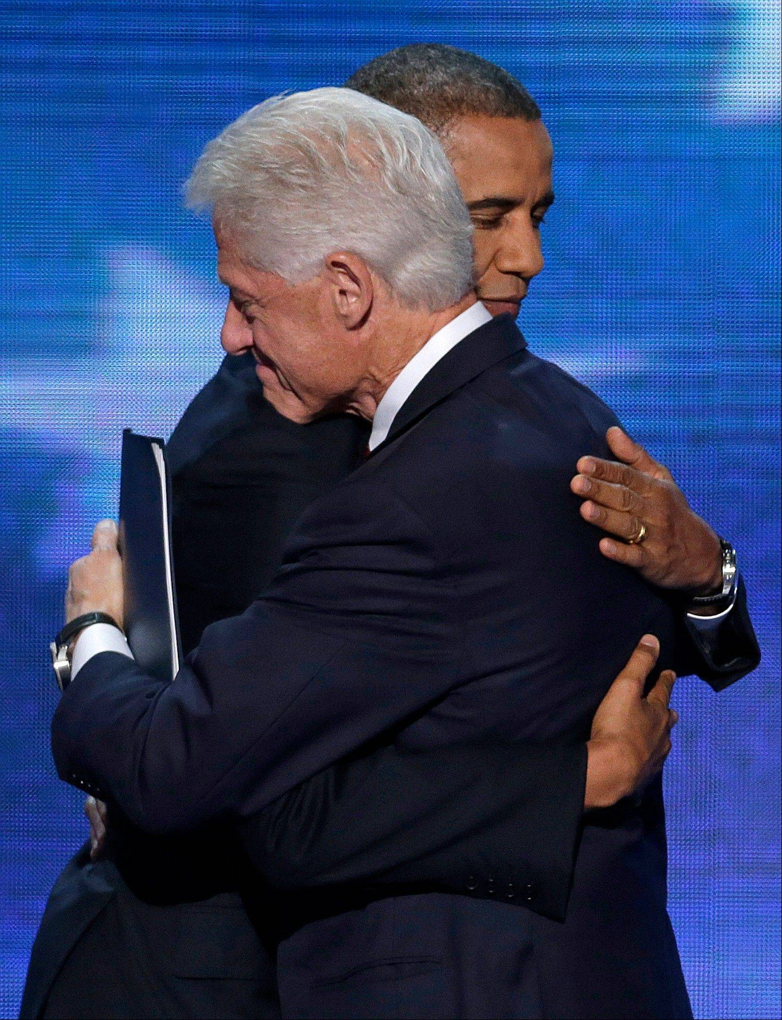 Former President Bill Clinton hugs President Barack Obama after President Obama walked on stage after Clinton's speech the Democratic National Convention in Charlotte, N.C., on Wednesday, Sept. 5, 2012.