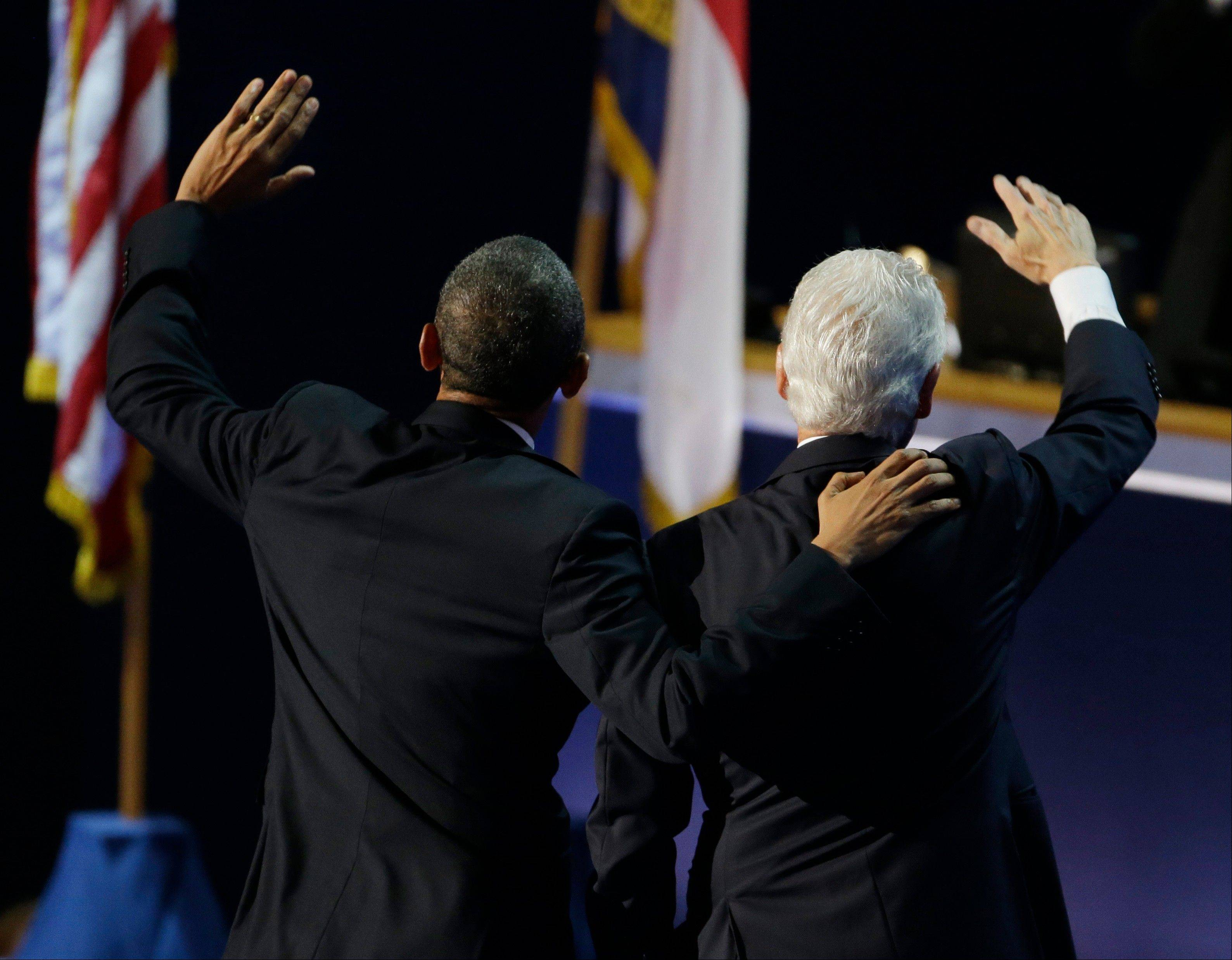 President Barack Obama, left, and former President Bill Clinton wave to delegates after Clinton's speech to the Democratic National Convention in Charlotte, N.C., on Wednesday, Sept. 5, 2012.