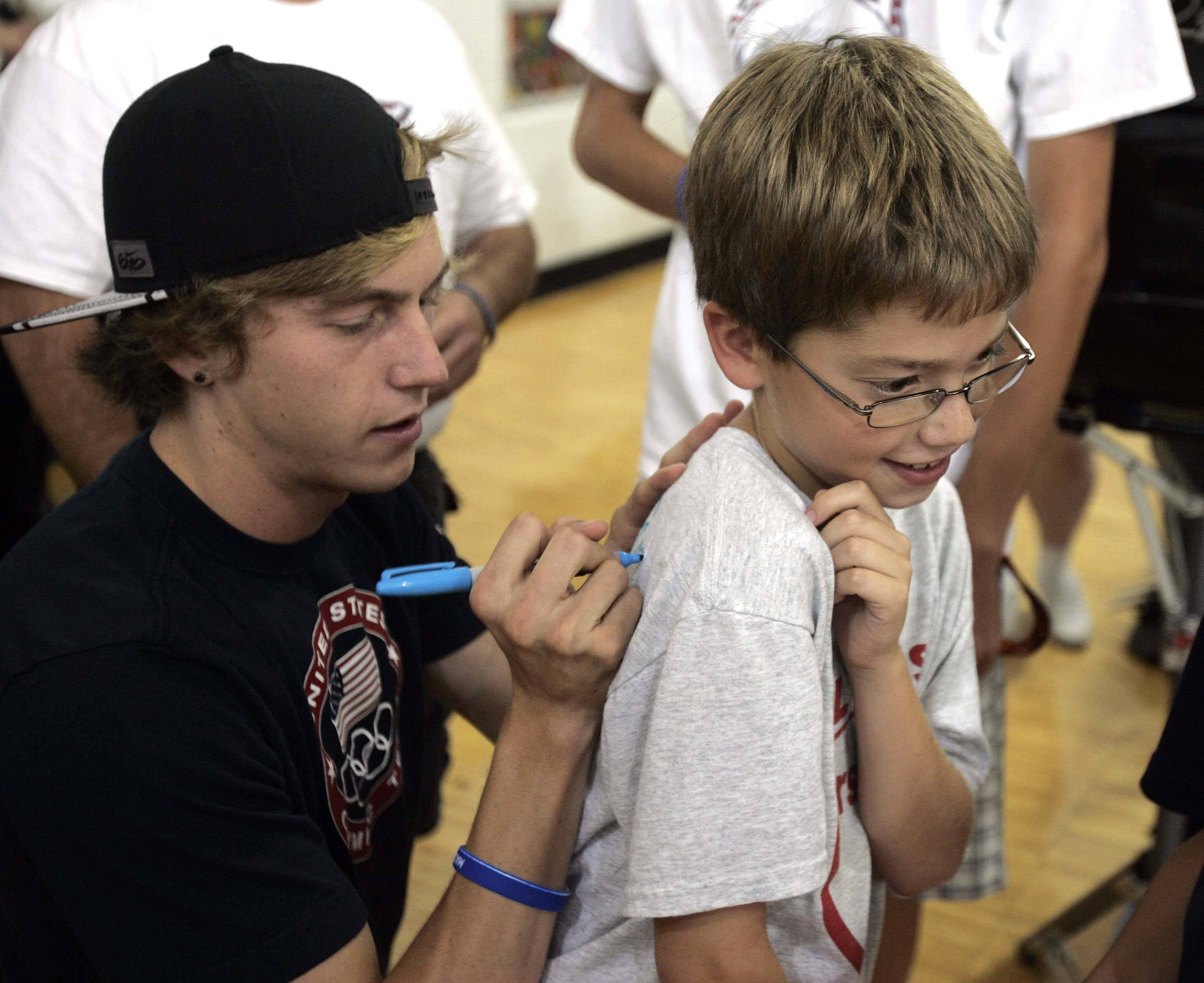 Nine-year-old Logan Marx of Algonquin gets his shirt signed by olympian Evan Jager who returned to H.D. Jacobs High School in Algonquin Wednesday.