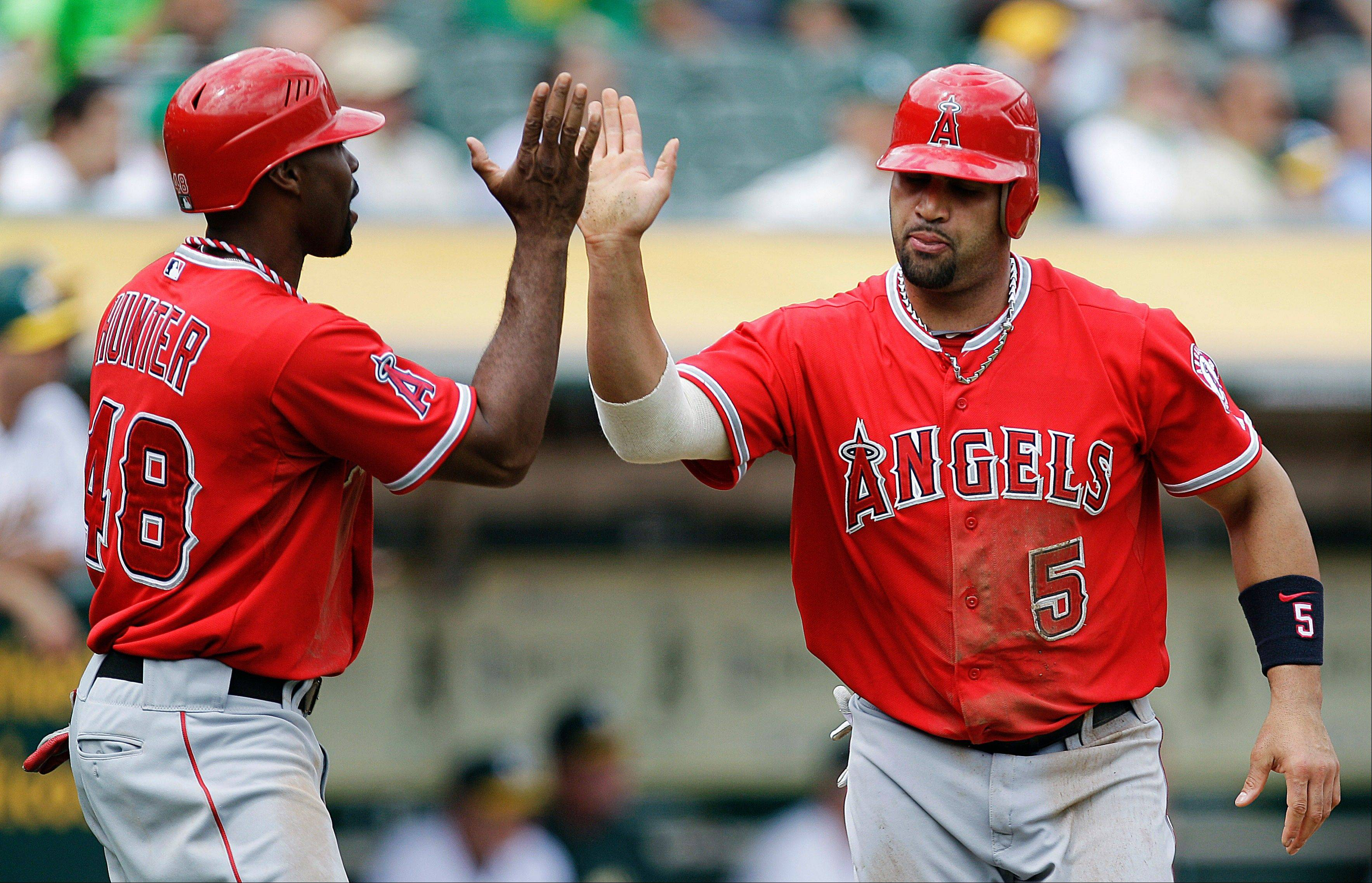 The Angels' Torii Hunter, left, and Albert Pujols celebrate after scoring against the Athletics in the third inning Wednesday in Oakland, Calif.