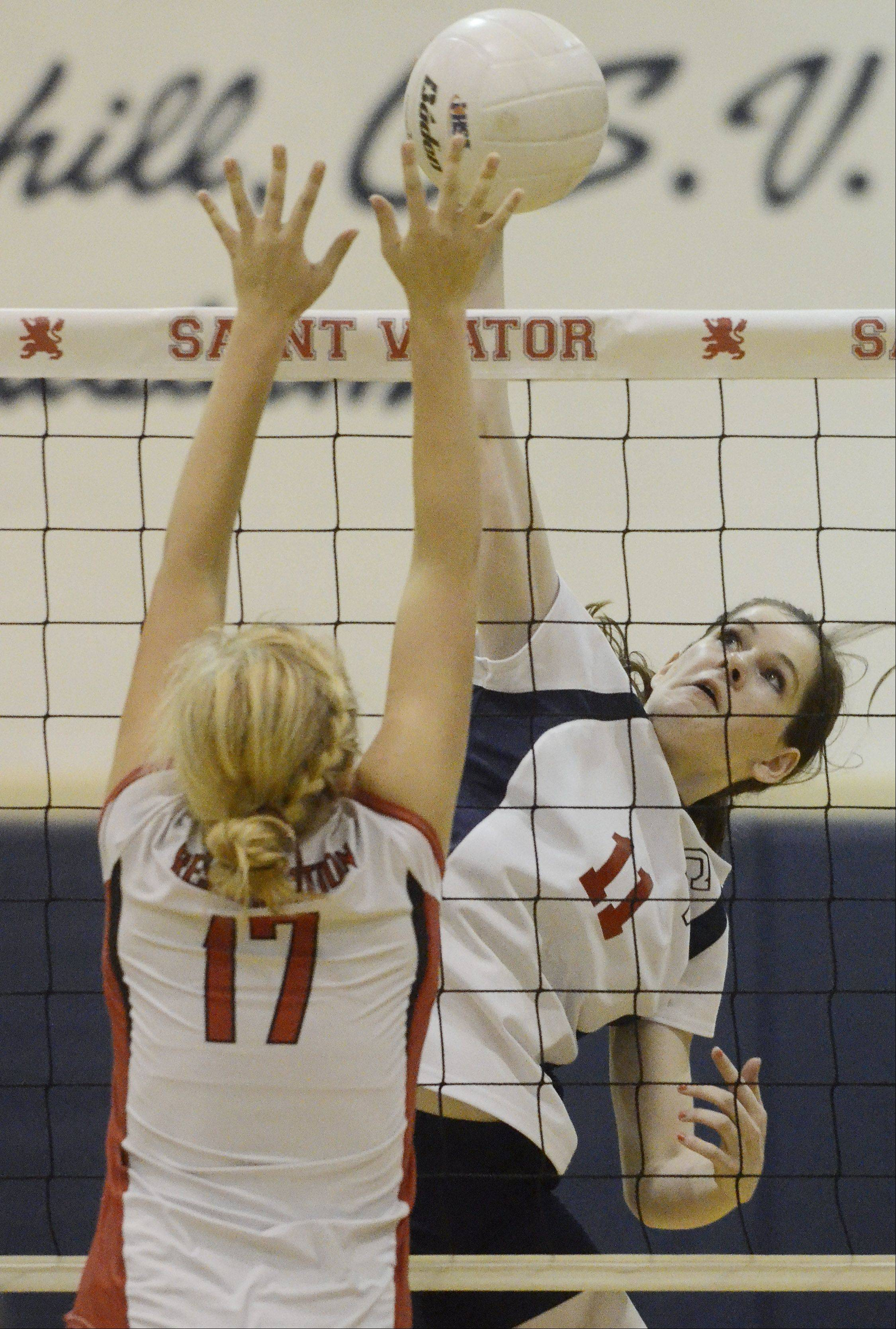 St. Viator's Lauren Mroz attempts a kill as Resurrection's Rachel Gotch leaps for a block Wednesday.
