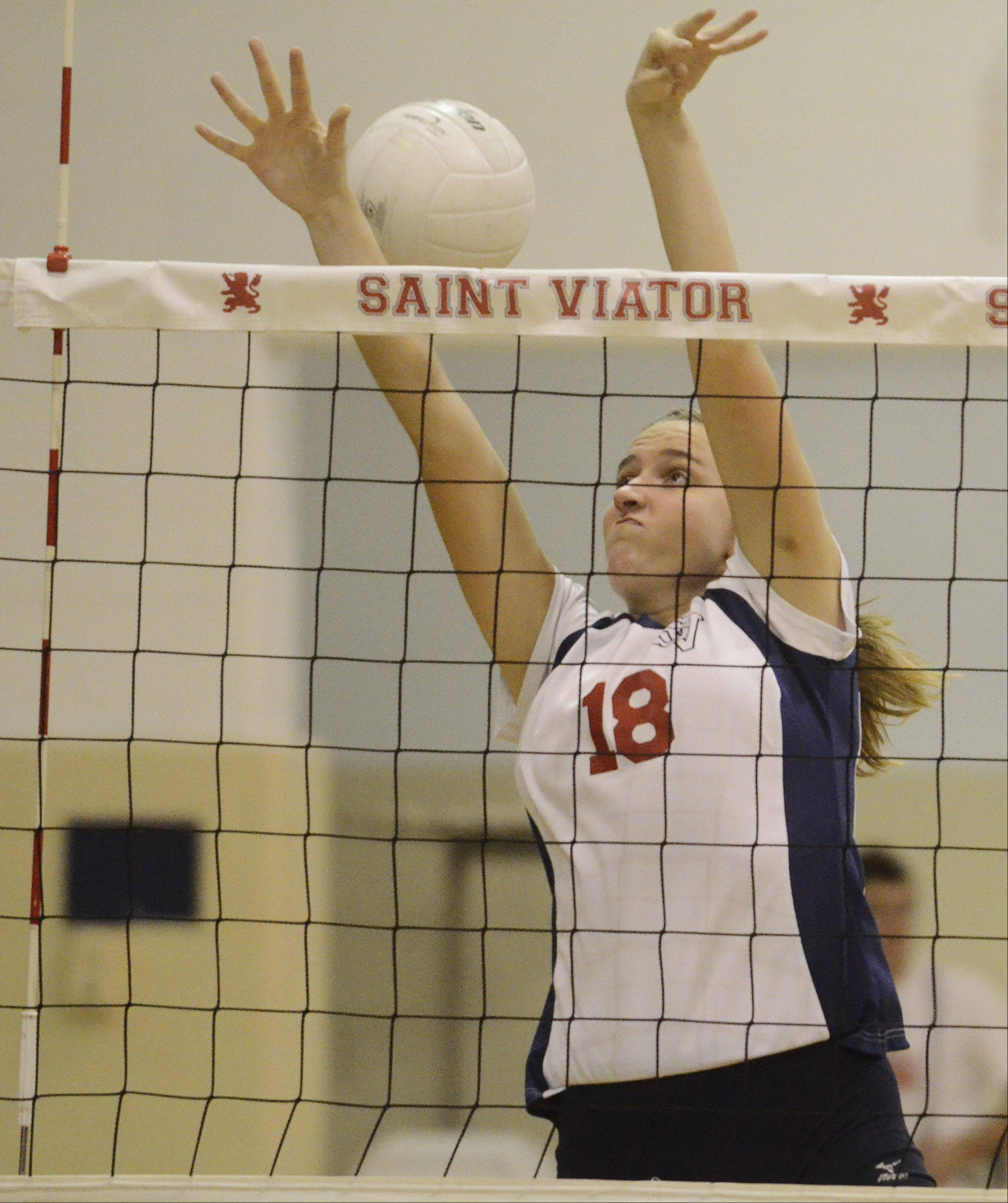 St. Viator's Mary Cleary tries to block a ball at the net during Wednesday's volleyball match against Resurrection.
