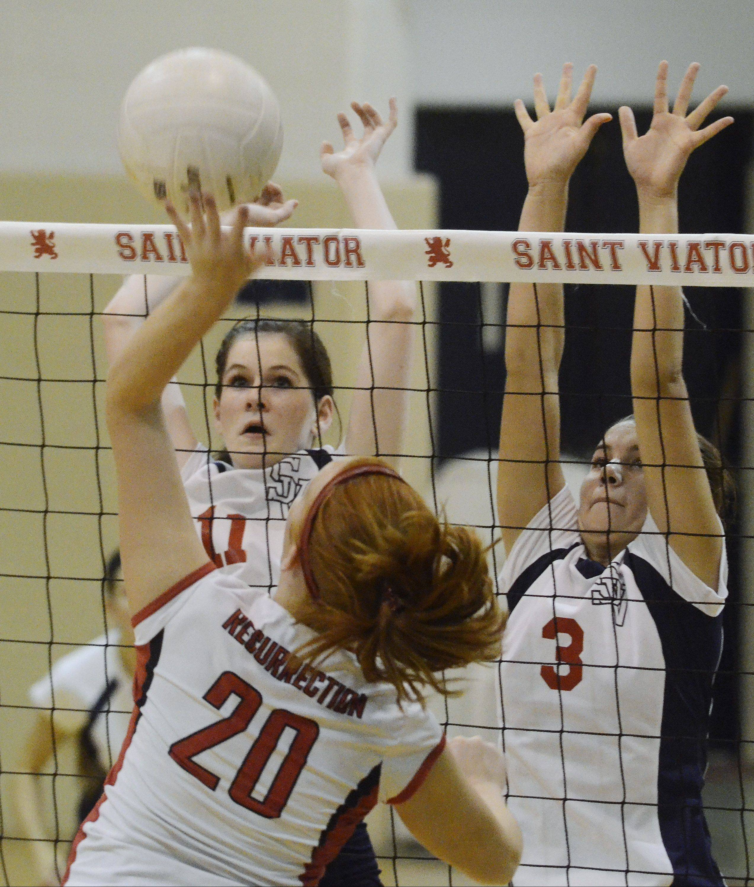 St. Viator's Lauren Mroz, left, and Megan Mueller, right, try to block a ball hit by Resurrection's Claire Moriarty during Wednesday's volleyball match.