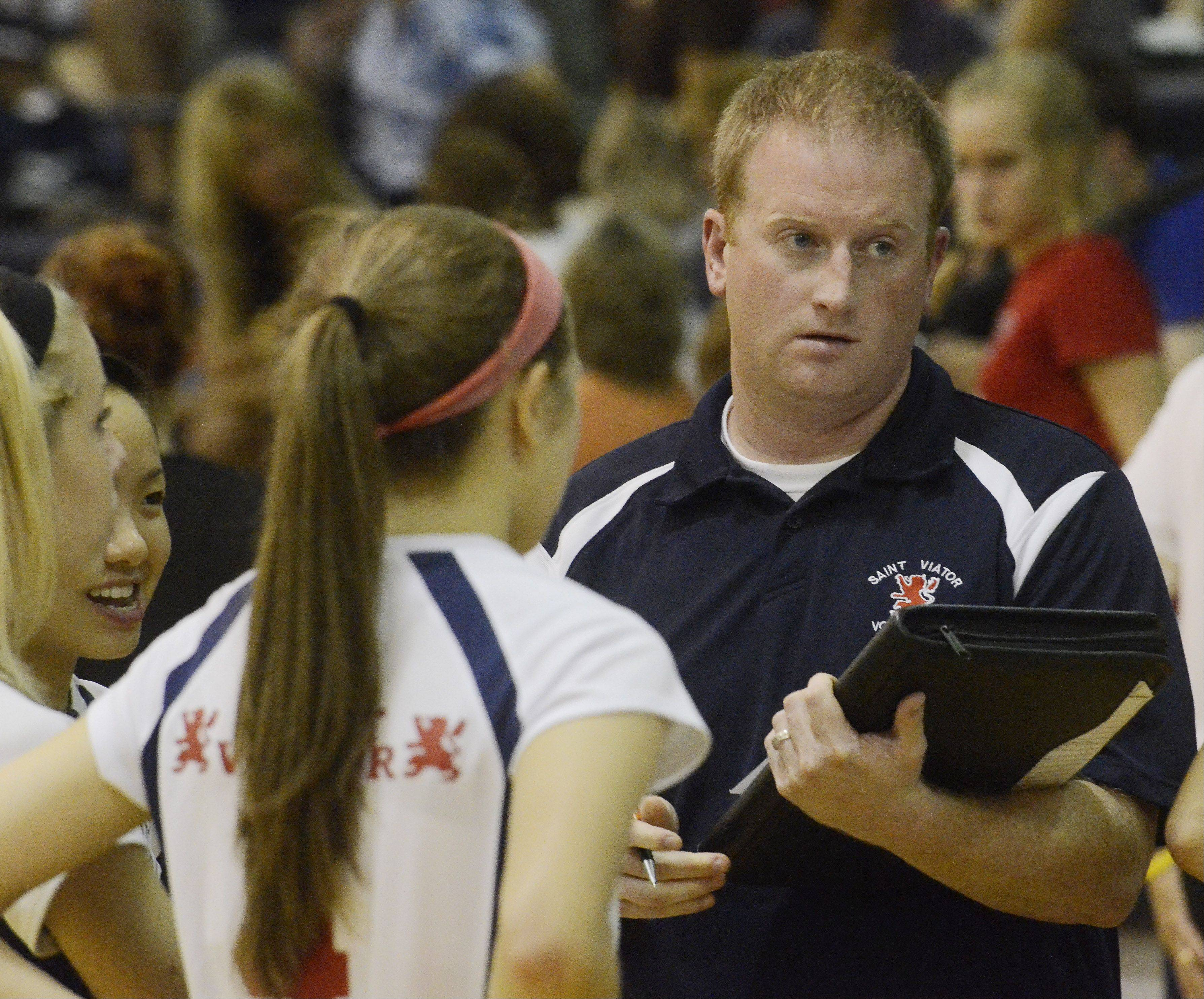 St. Viator girls volleyball coach Charlie Curtin talks to his team between games during Wednesday's match against Resurrection.