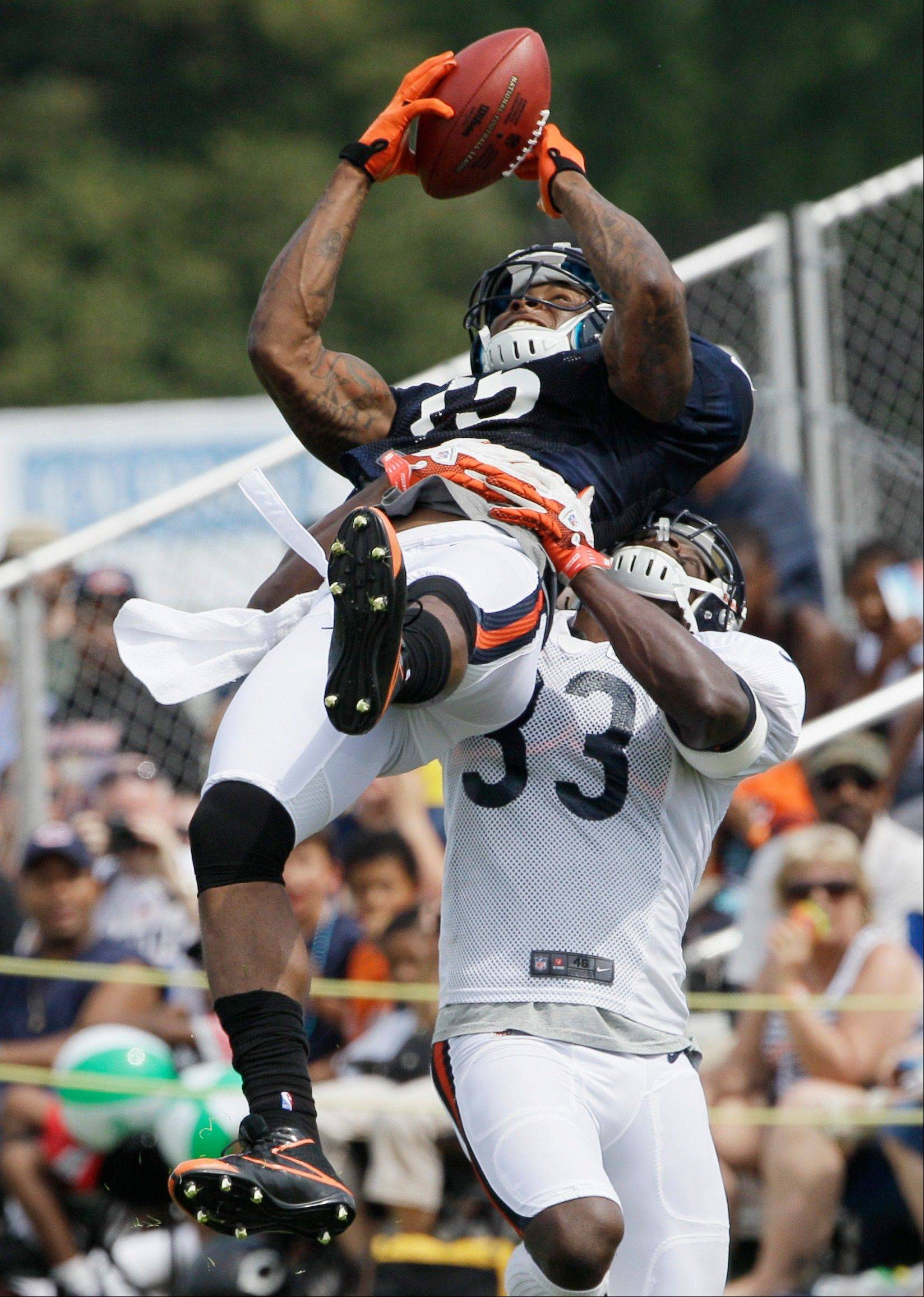 Chicago Bears wide receiver Brandon Marshall, top, catches a ball against cornerback Charles Tillman (33) during NFL football training camp at Olivet Nazarene University in Bourbonnais, Ill., Sunday, July 29, 2012.