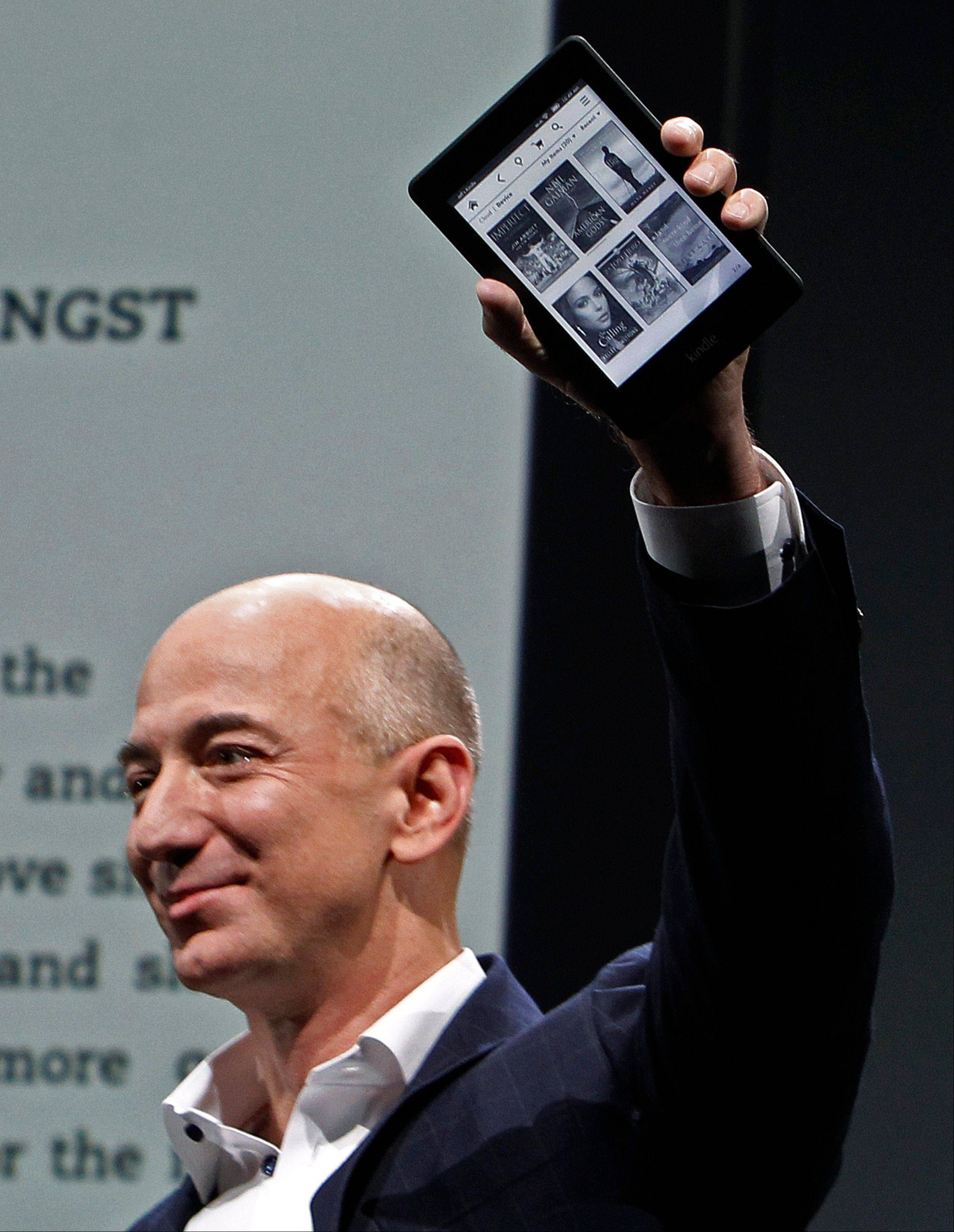Jeff Bezos, CEO and founder of Amazon, holds the Kindle Paperwhite at the introduction of the new Amazon Kindle Fire HD and Paperwhite devices in Santa Monica, Calif., Thursday.