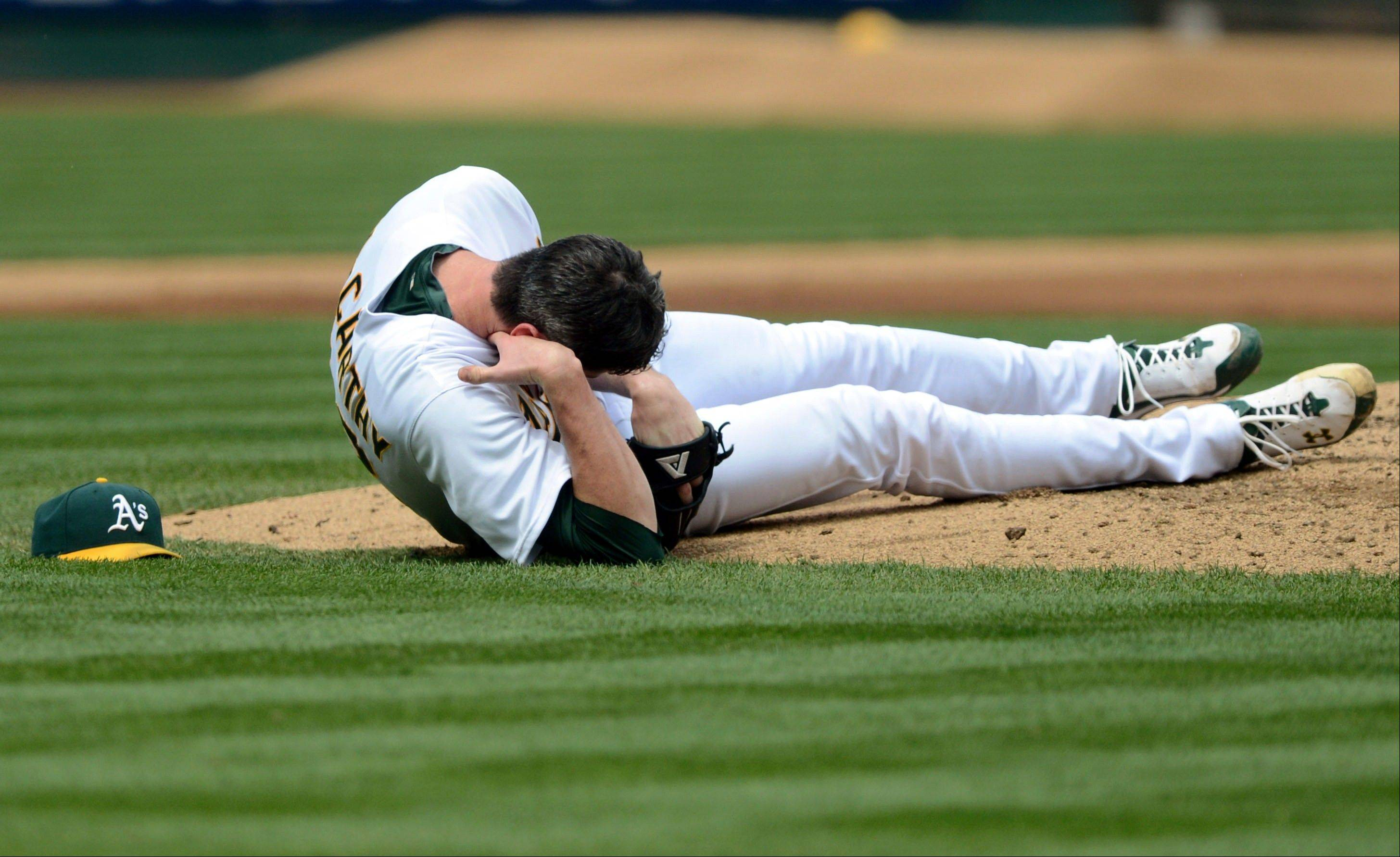 Oakland pitcher Brandon McCarthy holds his head after being struck by a ball hit by the Angels� Erick Aybar in the fourth inning Wednesday at home. He underwent surgery on Thursday.