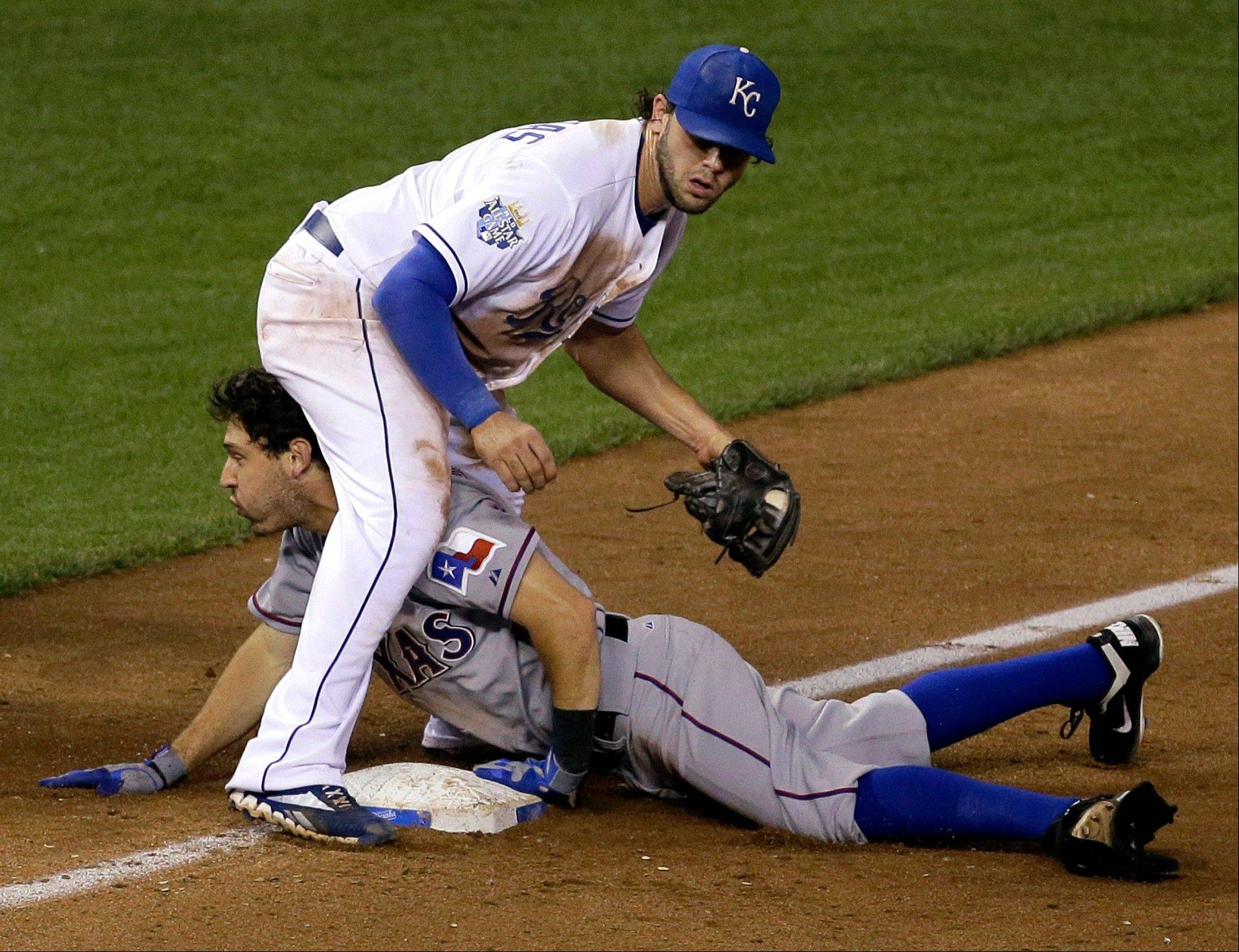 The Rangers� Ian Kinsler beats the tag by Royals third baseman Mike Moustakas for a triple during the 10th inning Thursday night in Kansas City.