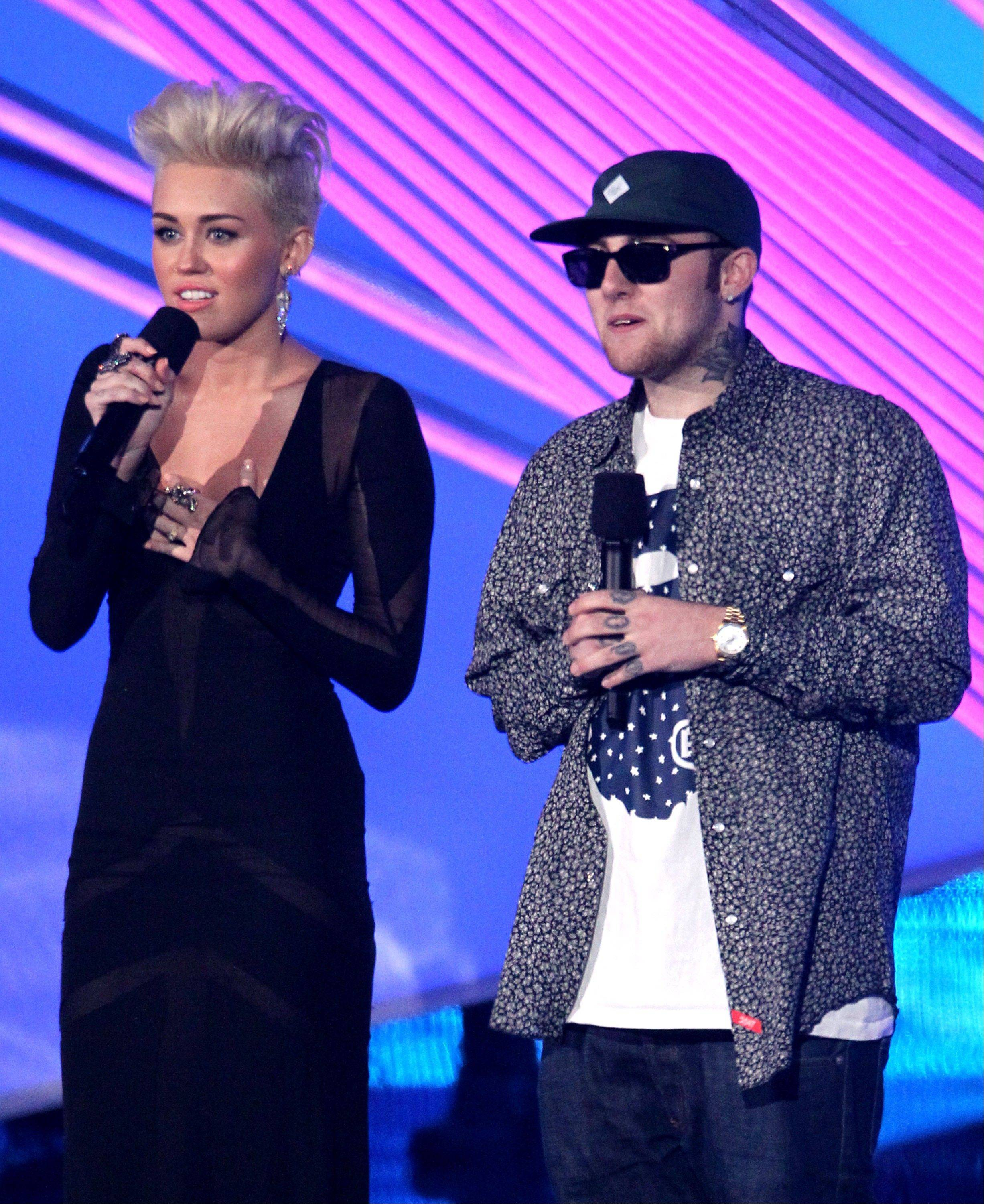Miley Cyrus, left, and Mac Miller present an award onstage at the MTV Video Music Awards on Thursday, Sept. 6, 2012, in Los Angeles.