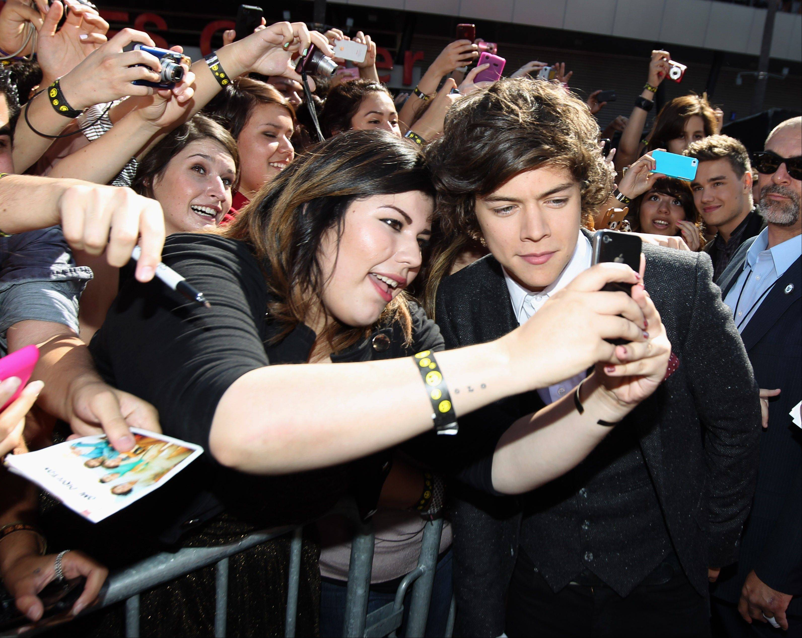 Harry Styles, right, of the British band One Direction greets fans at the MTV Video Music Awards on Thursday, Sept. 6, 2012, in Los Angeles.