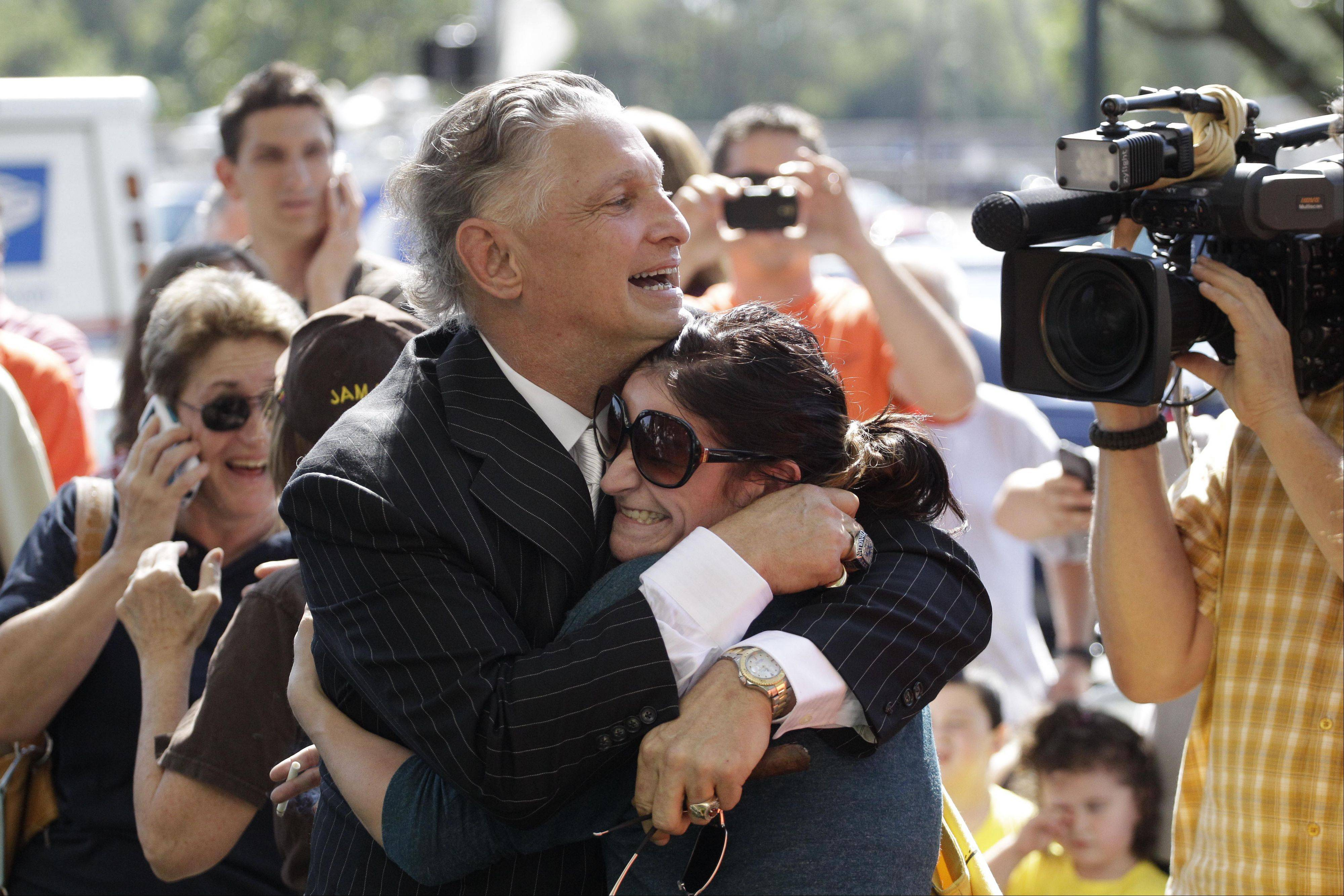 Jeff Ruby and Stephanie Freitage embrace outside the Will County Courthouse after word spread that former Bolingbrook police officer Drew Peterson was found guilty of murdering his third wife Kathleen Savio Thursday, Sept. 6, 2012, in Joliet, Ill.