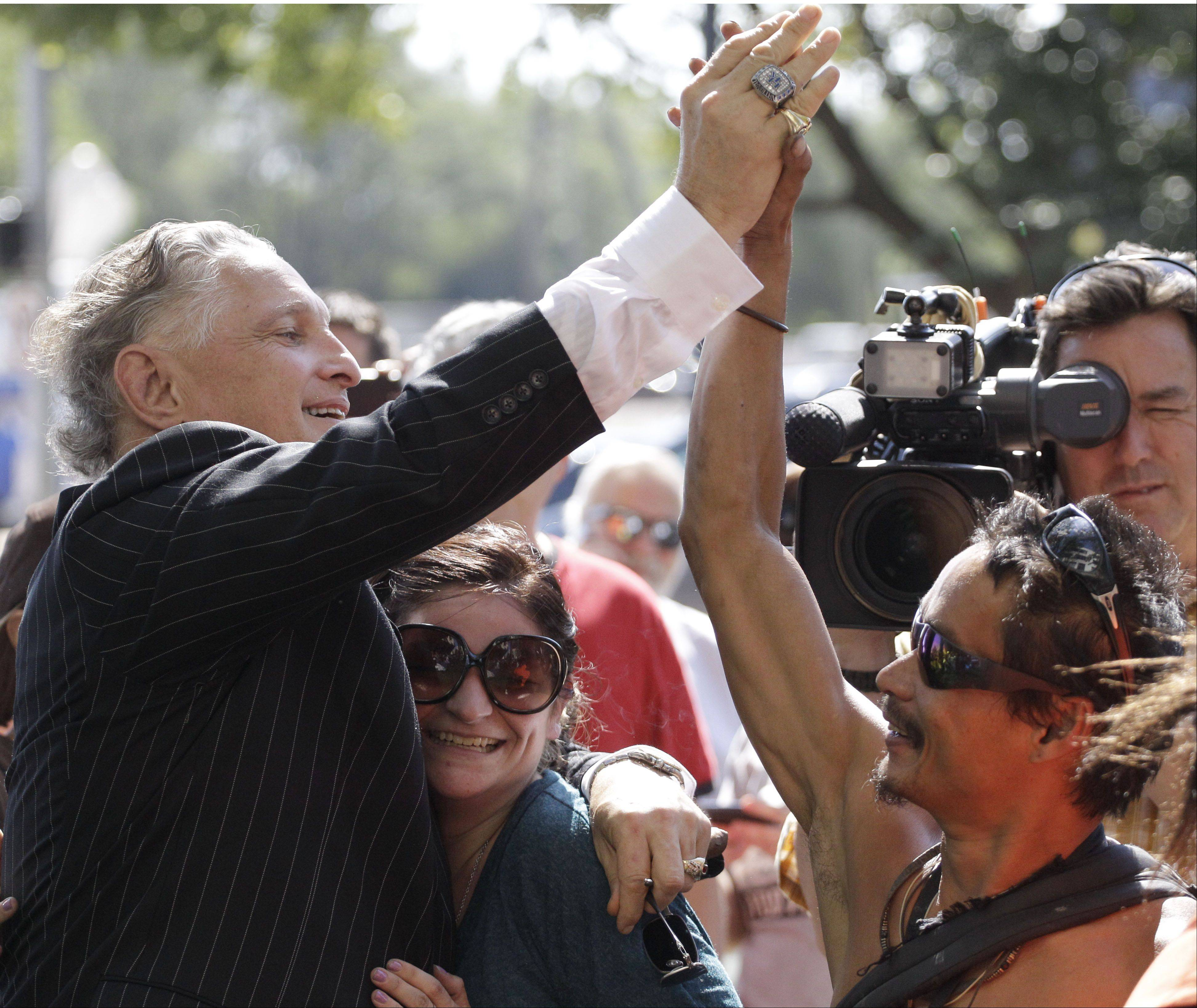Jeff Ruby high fives Donald Shiner and hugs Stephanie Freitage outside the Will County Courthouse after word spreads that former Bolingbrook police officer Drew Peterson was found guilty of murdering his third wife Kathleen Savio Thursday, Sept. 6, 2012, in Joliet, Ill.