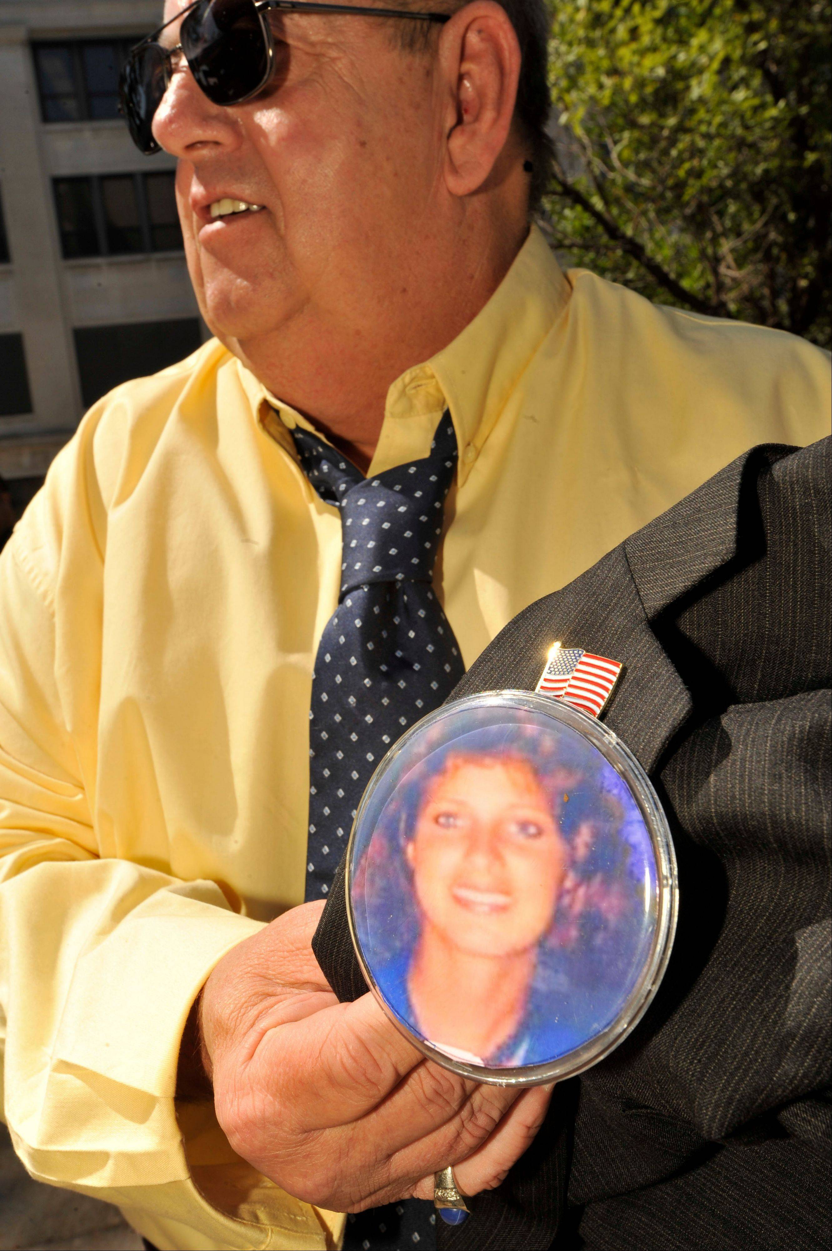 Mitch Doman, brother-in-law of Kathleen Savio, holds a photo button of late Savio outside the Will County Courthouse during the second day of jury deliberations in former Bolingbrook police officer Drew Peterson's murder trial, Thursday, Sept. 6, 2012, in Joliet, Ill.