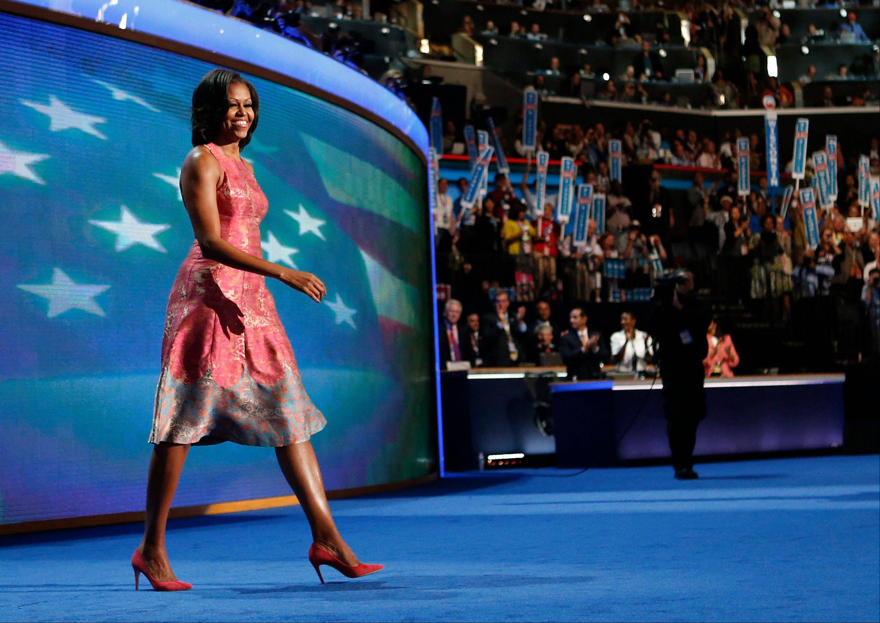 "First lady Michelle Obama walks onto the stage at the Democratic National Convention in Charlotte, N.C. Tracy Reese, who designed Obama's hot pink silk jacquard dress with pale blue trim at the hem, says she's rushing to make more of them. She told NBC's ""Today"" show that the dress will cost under $500."