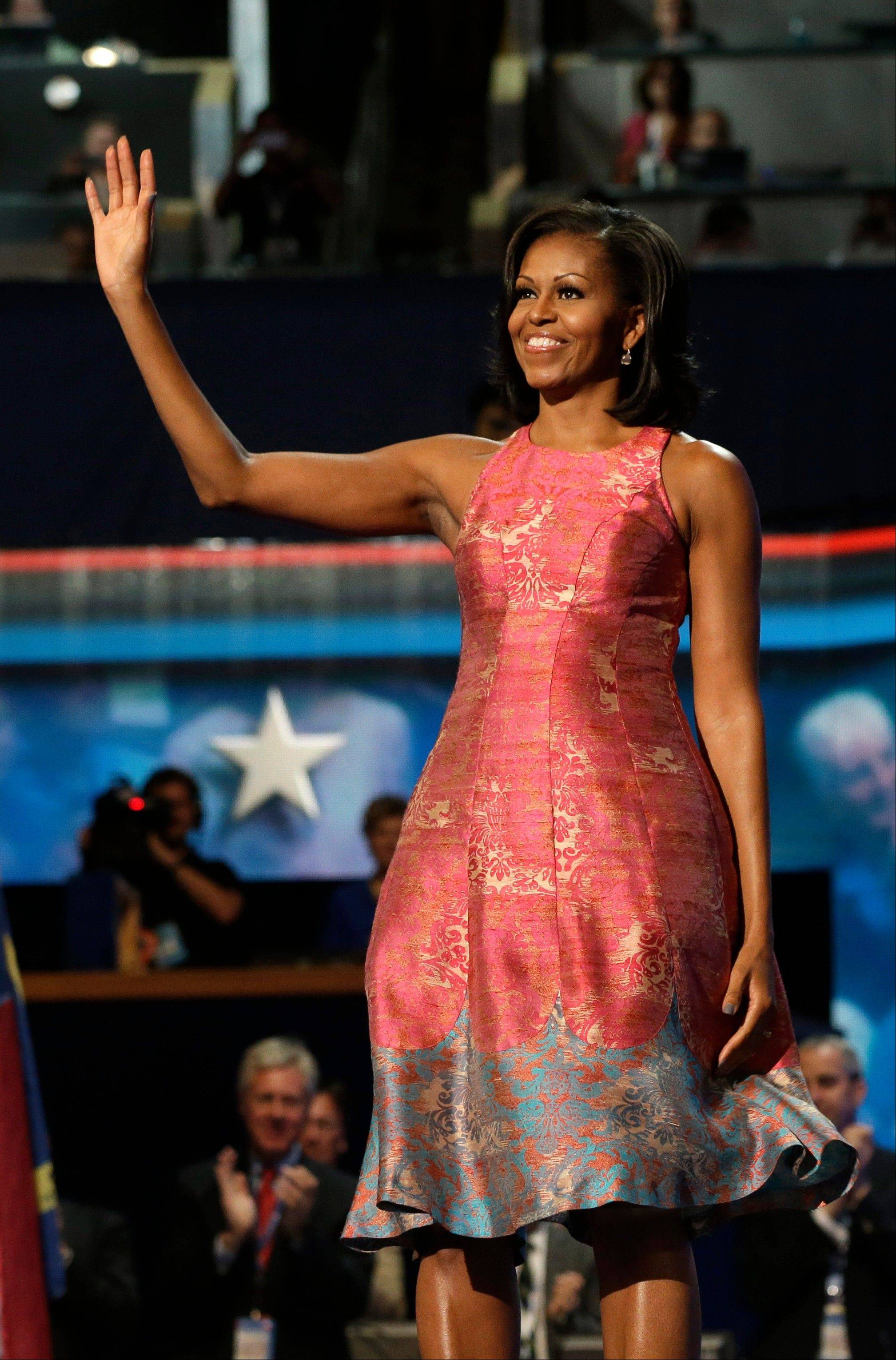 "First lady Michelle Obama waves to delegates at the Democratic National Convention in Charlotte, N.C. Tracy Reese, who designed Obama's pink silk jacquard dress with pale blue trim at the hem, says she's rushing to make more of them. Reese told NBC's ""Today"" show that the dress will cost under $500."