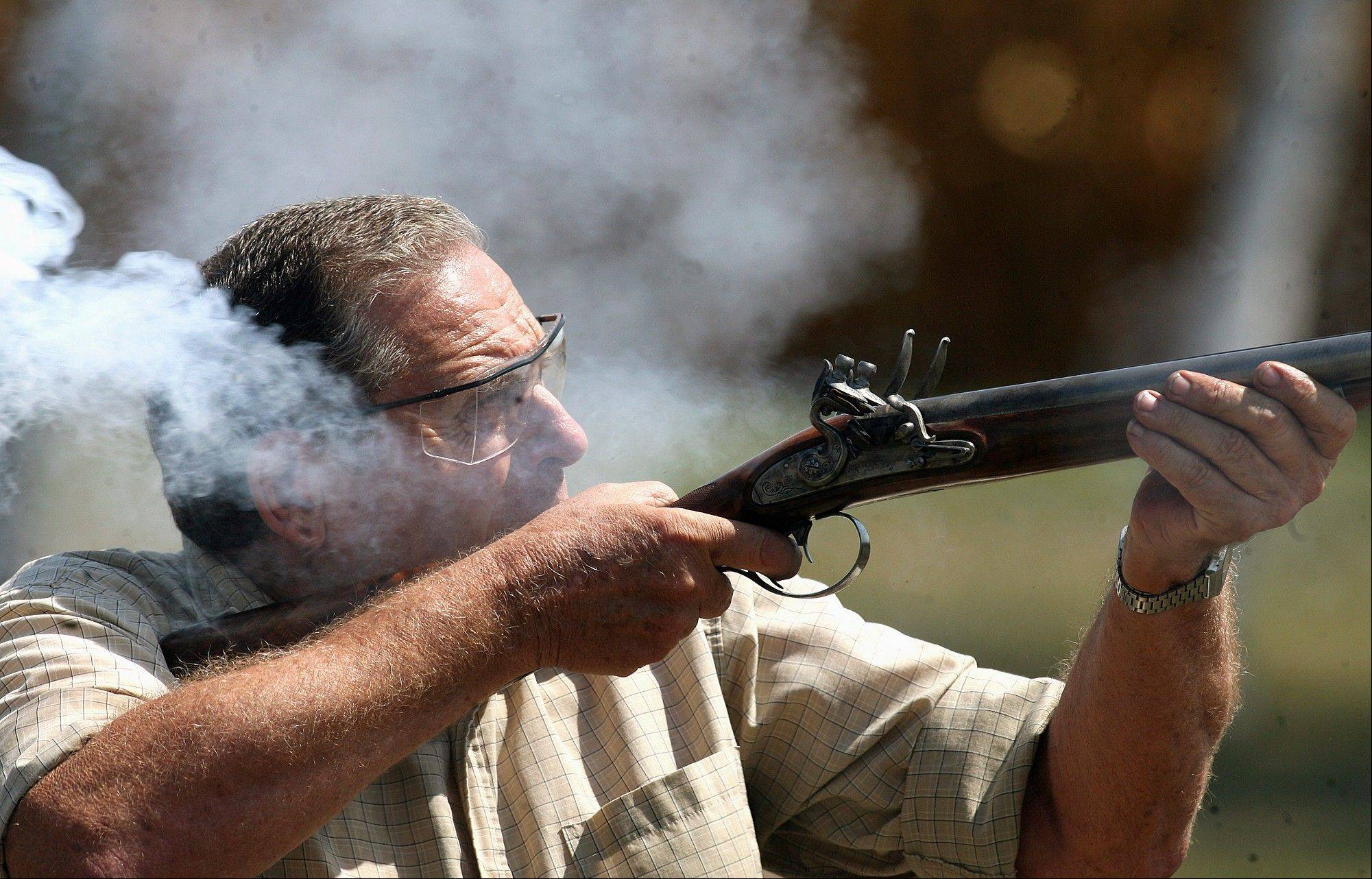 Chuck Lindsey fires a double-barreled, flintlock shotgun he built during trapshooting practice with friends in rural southwest Logan County. Lindsey builds muzzleloading firearms, especially flintlocks that were in use in the late 18th and early 19th centuries.