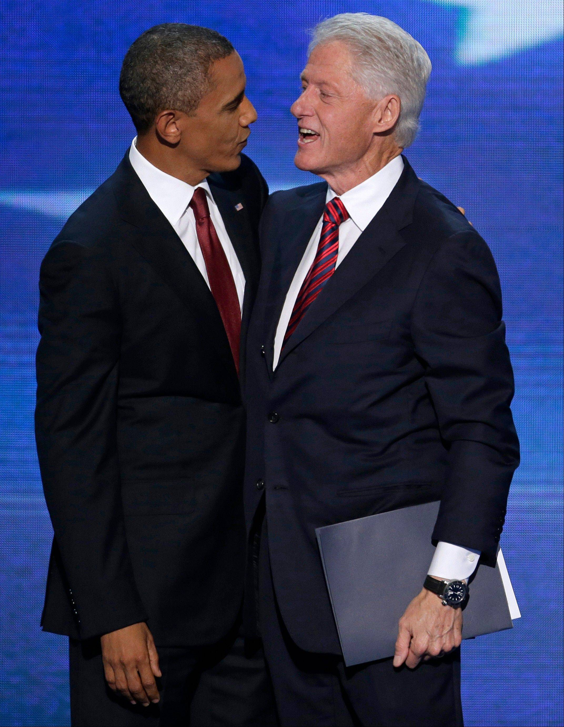 Former President Bill Clinton talks with President Barack Obama after Clinton's speech to the Democratic National Convention in Charlotte, N.C., on Wednesday.