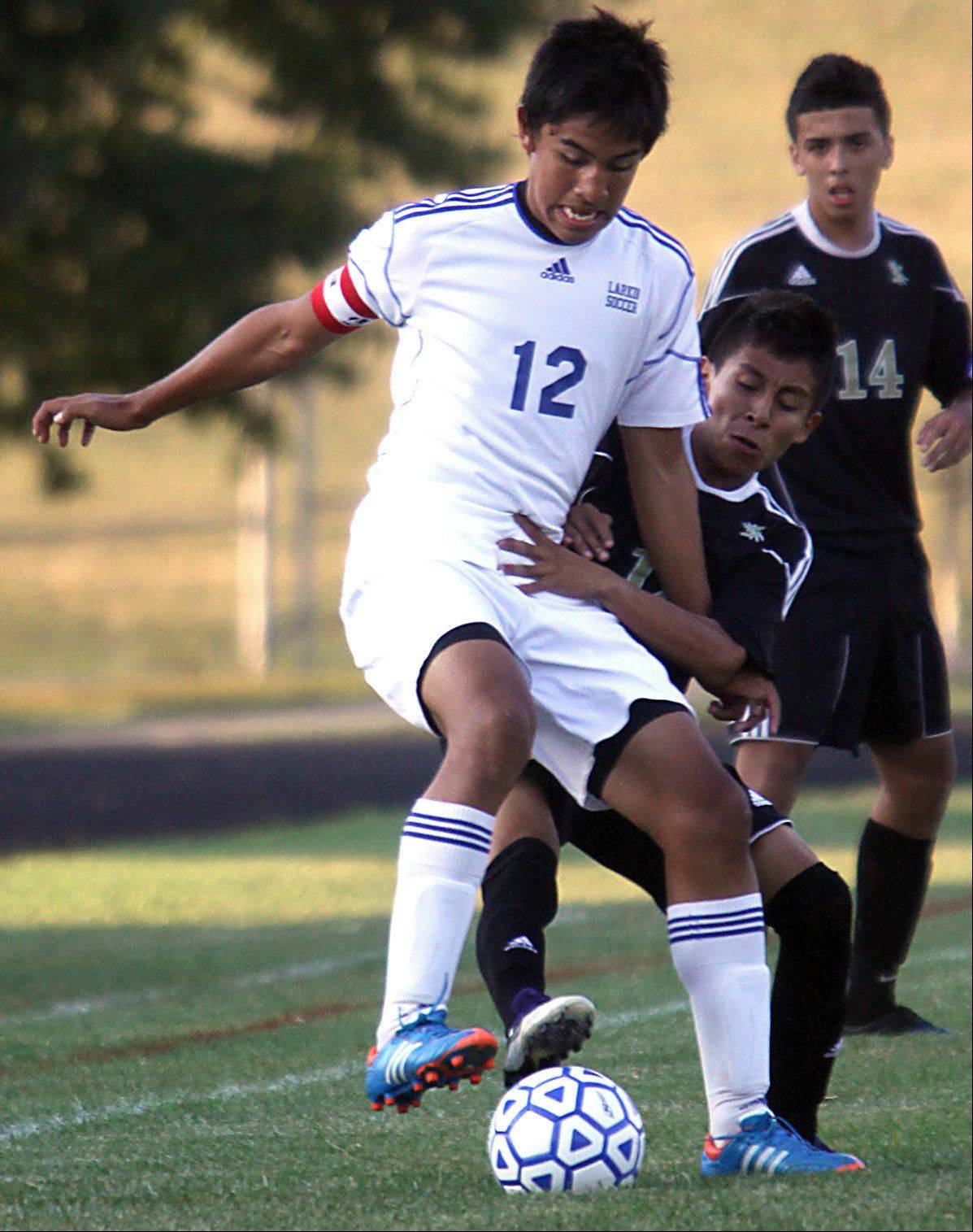 Larkin's Tony Hernandez, left, battles Streamwood's Edwin Rueda, right, for control of the ball during a varsity soccer game at Memorial Field in Elgin on Thursday night.