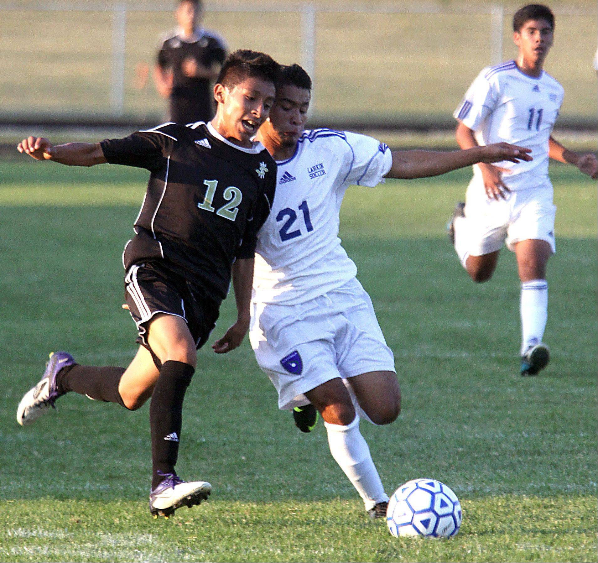Larkin's Junior Escalante, right, races Streamwood's Edwin Rueda, left, to the ball during a varsity soccer game at Memorial Field in Elgin on Thursday night.