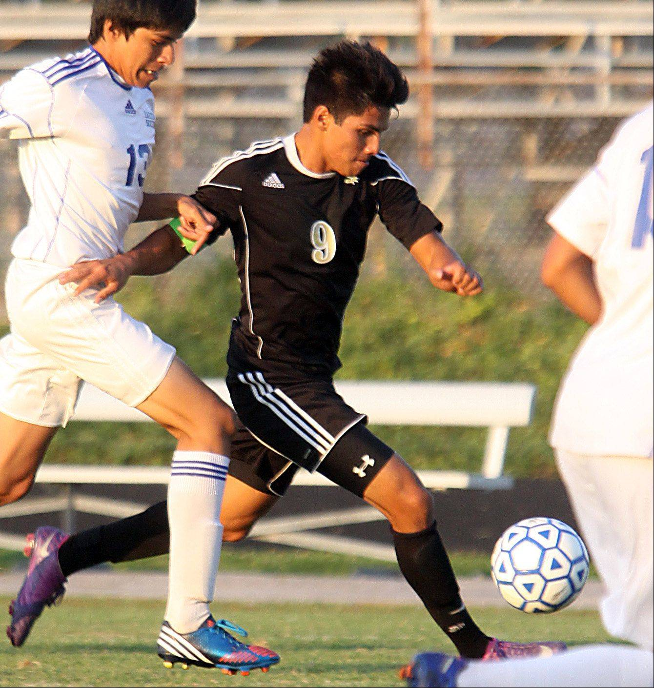 Larkin's Hector Mendoza, left, tries to catch Streamwood's Mario Rodriguez, center, during a varsity soccer game at Memorial Field in Elgin on Thursday night.