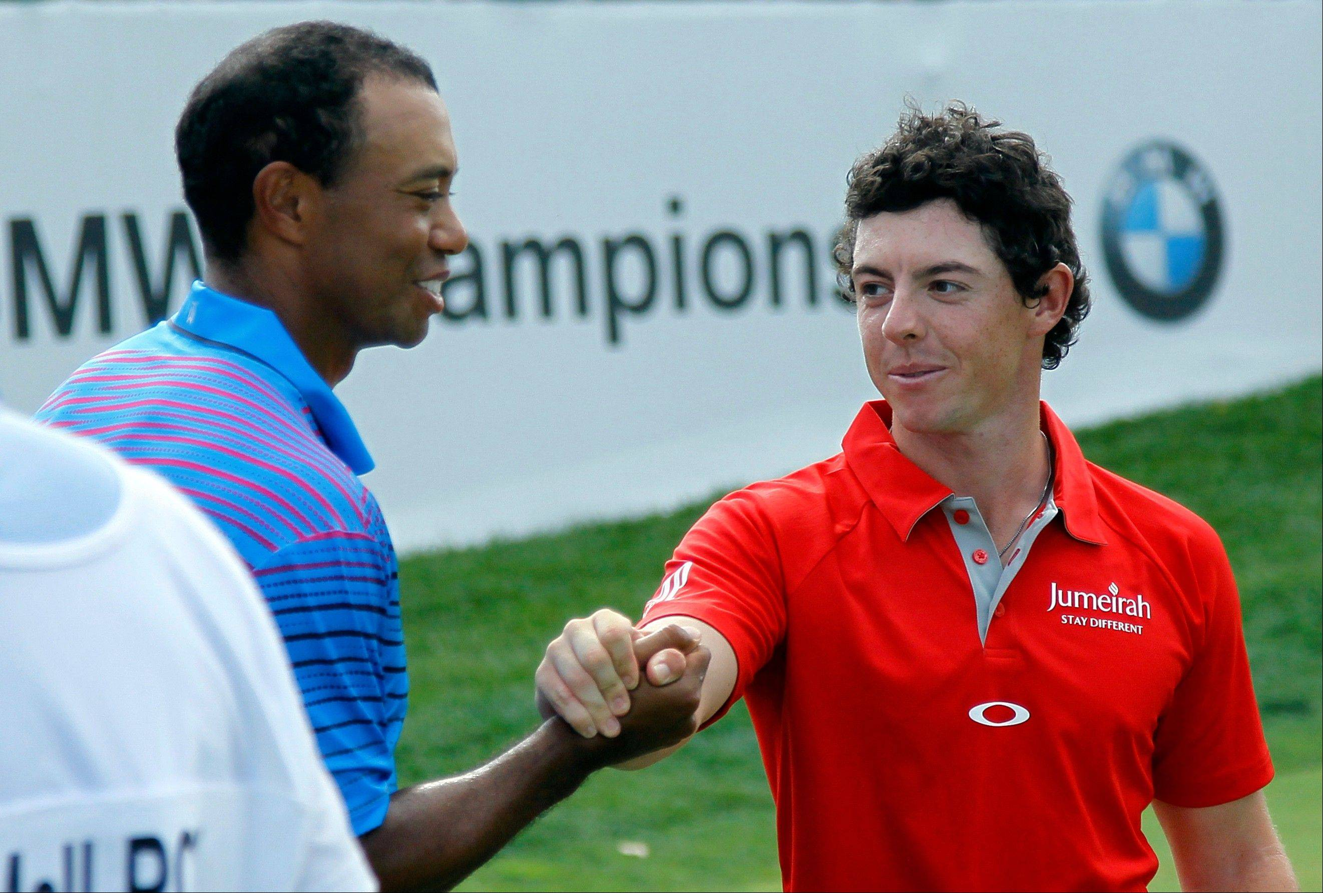Tiger Woods and Rory McIlroy shake hands Thursday after the first round of the BMW Championship golf tournament at Crooked Stick Golf Club in Carmel, Ind.