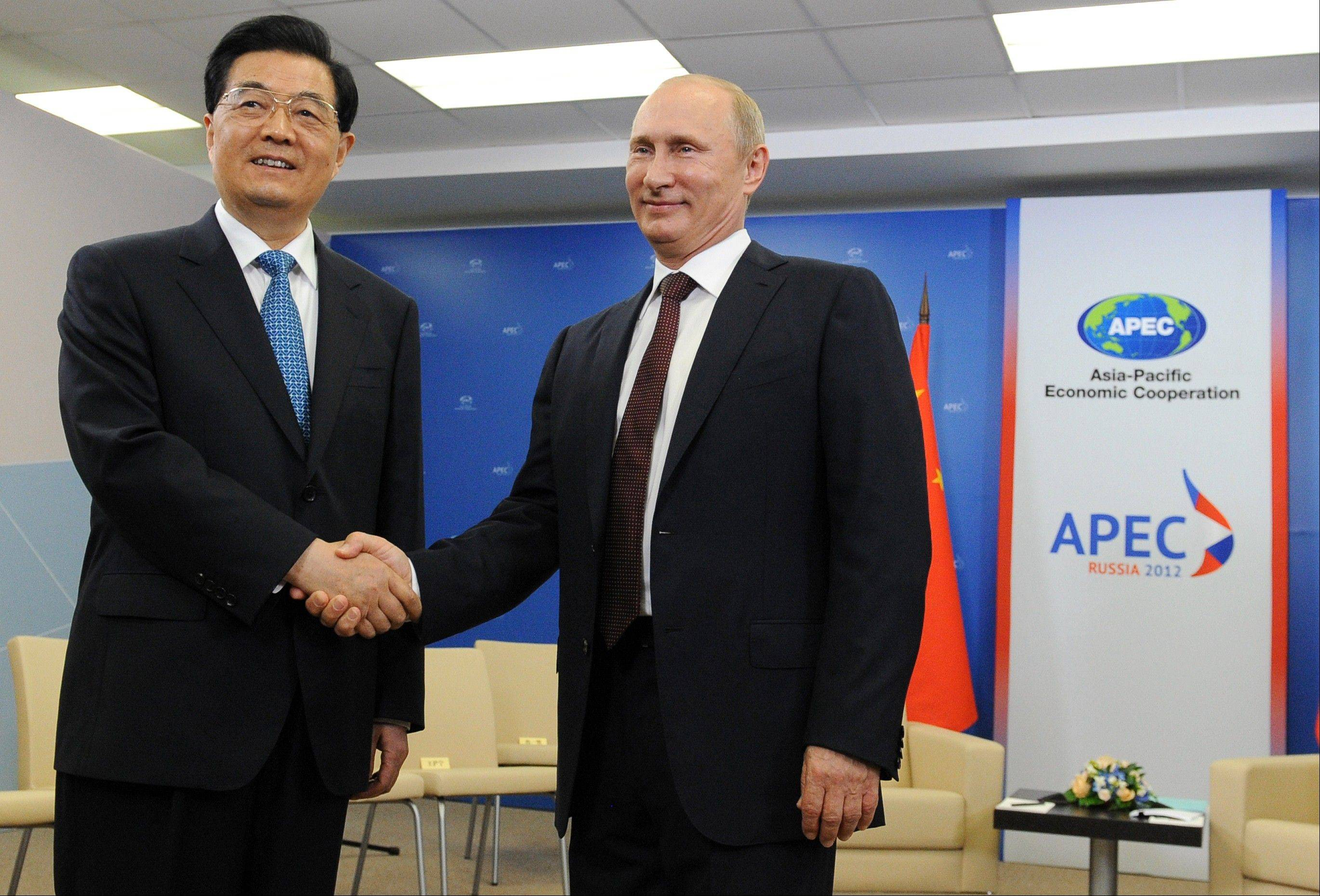 In this photo released by APEC, Russian President Vladimir Putin, right, meets with Chinese President Hu Jintao Friday during the APEC summit in Vladivostok, Russia.