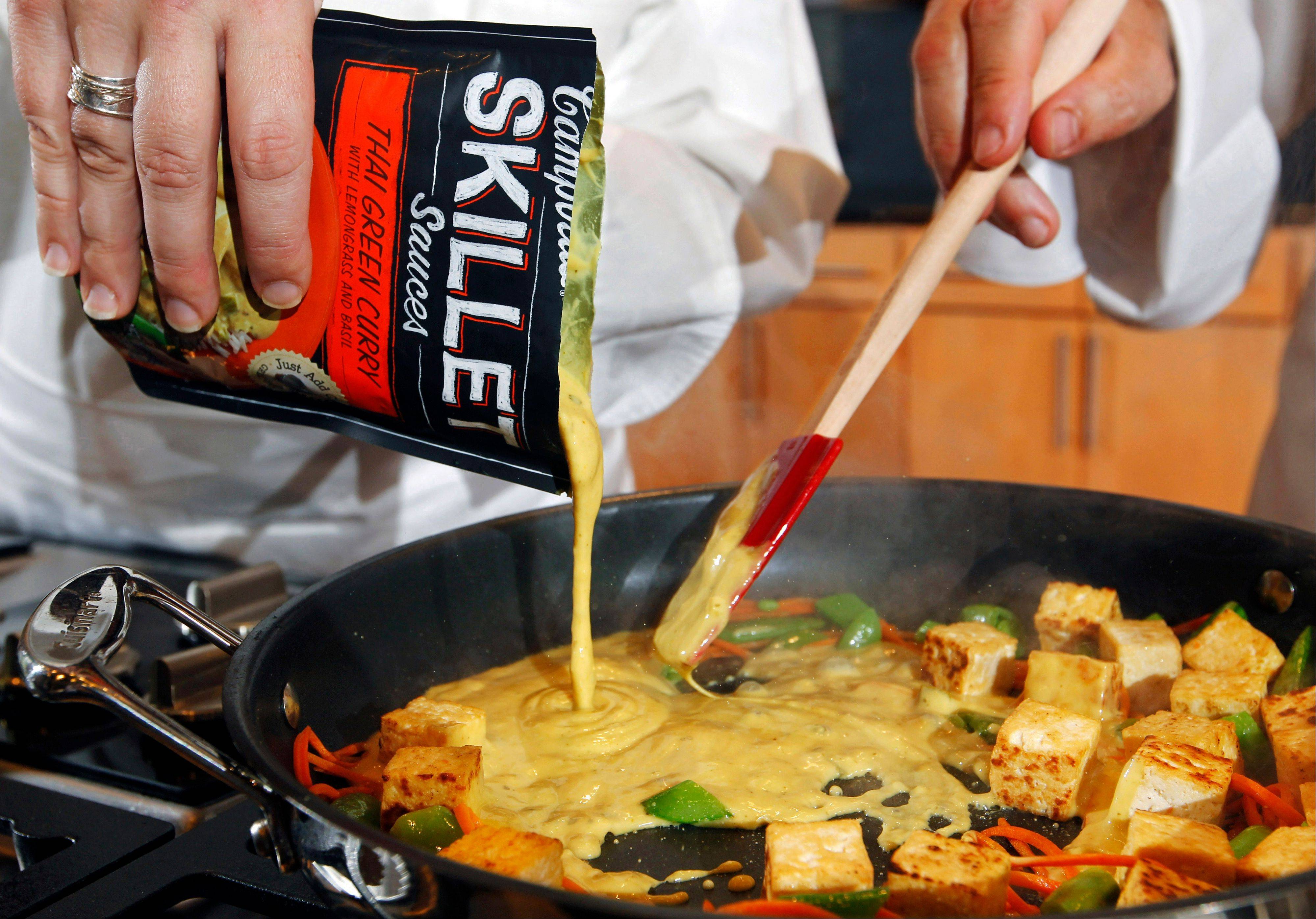 Campbell�s new Green Thai Curry Skillet sauce is poured over fresh produce and tofu at the Campbell Soup Company headquarters in Camden, N.J. Last year the company began a quest that led executives to trendsetting cities including Portland, Ore. and London to figure out how to make soups that appeal to younger, finicky customers. In the year ahead, the 143-year-old company plans to roll out 50 new products such as Moroccan Style Chicken and Spicy Chorizo.