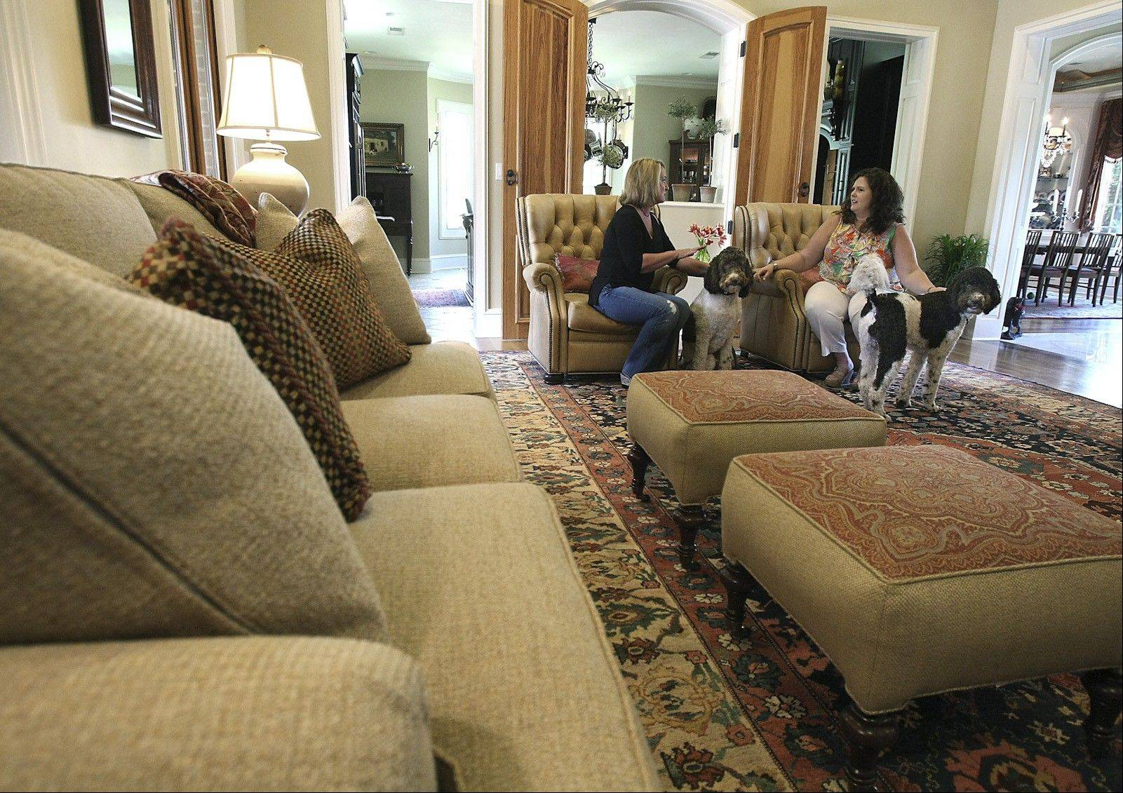 Rita Christian, left, and Stacy McSpadden relax in a pair of U.S.-made, matching aniline dyed leather recliners from Hancock and Moore. Also shown are Christian�s Labradoodles, Napoleon and Josephine