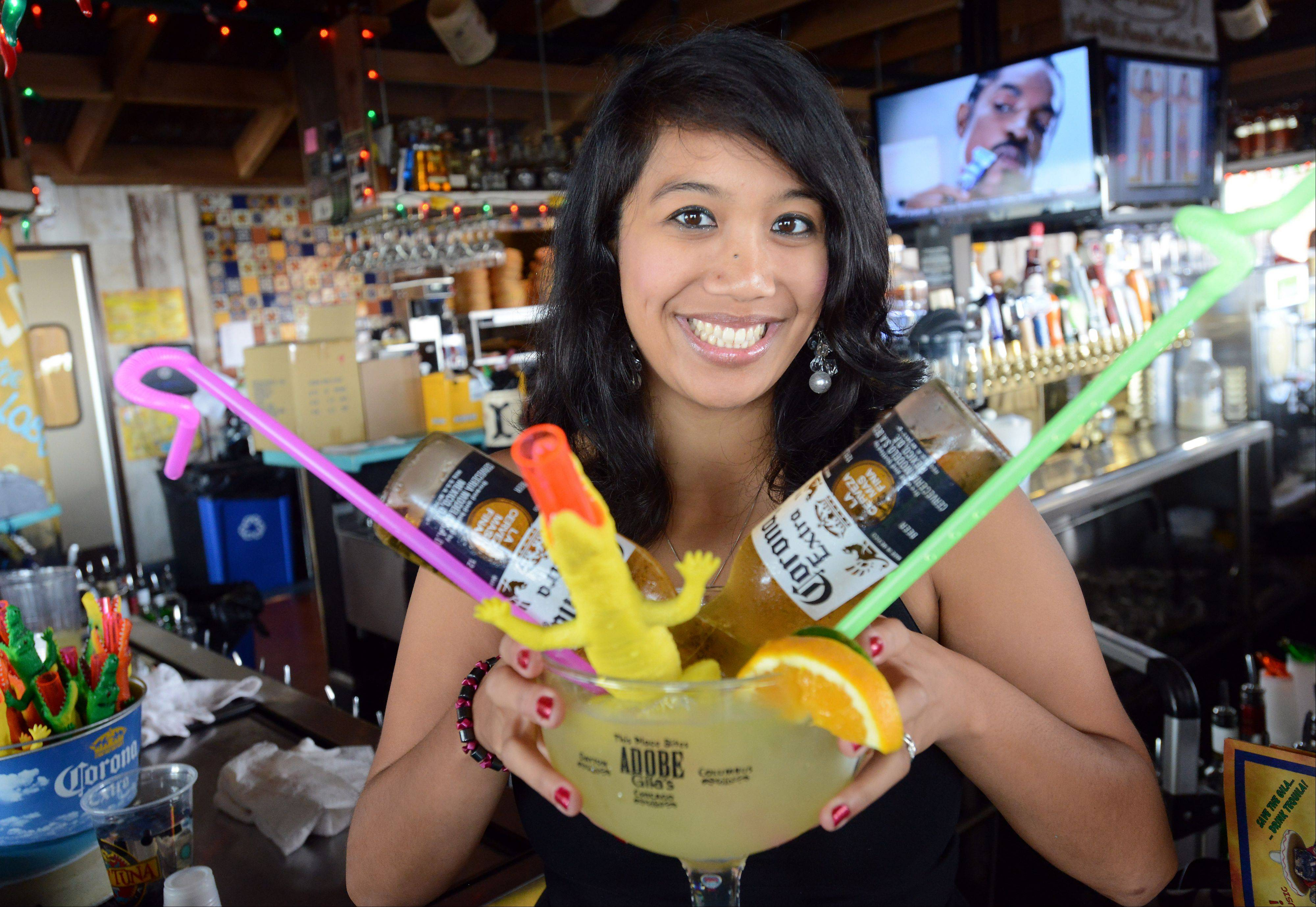 Bartender Cheryl Yu serves up mongo margaritas at Adobe Gila's in Rosemont.