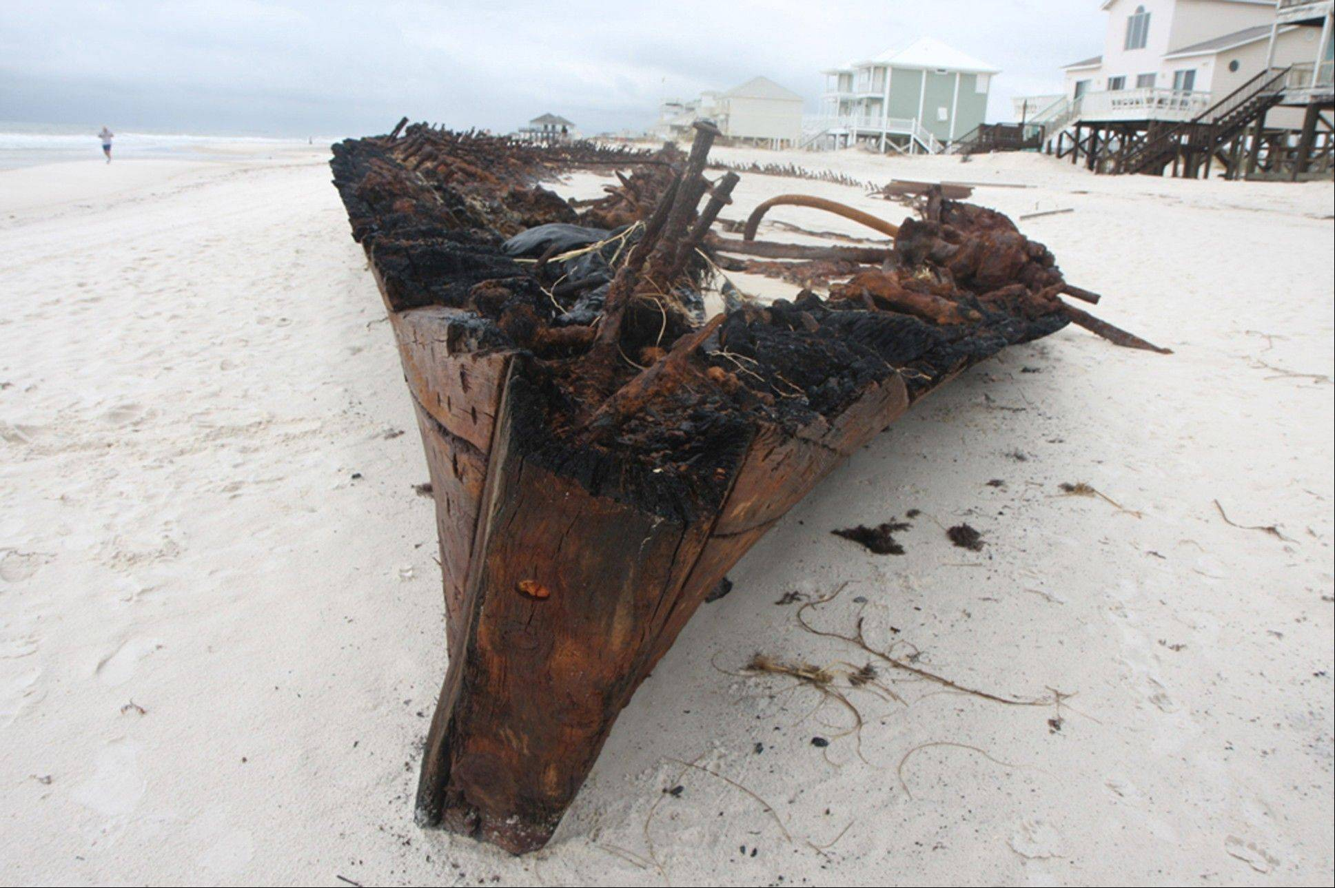 The ghostly remains of an old wooden ship rest Wednesday along a private beach at Fort Morgan, Ala.