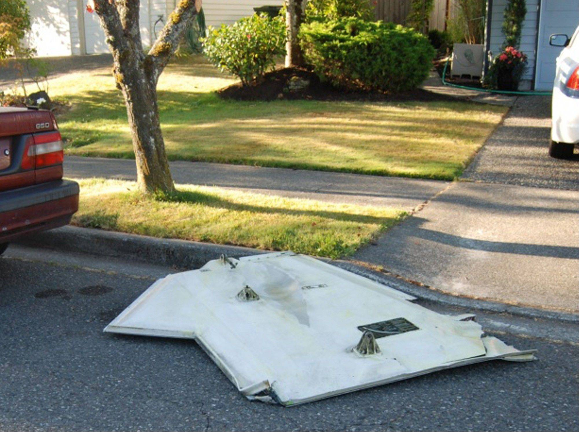 In this photo provided by Leah Dermody, a piece of metal that appears to be a landing gear door from an airplane is lying on the street Friday.
